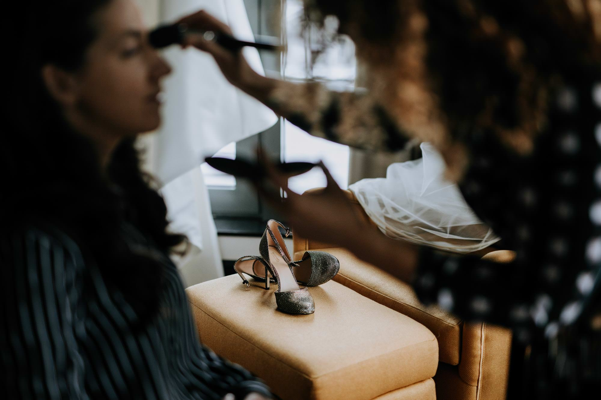 bride's shoes are in focus in the background while bridesmaid gets makeup done