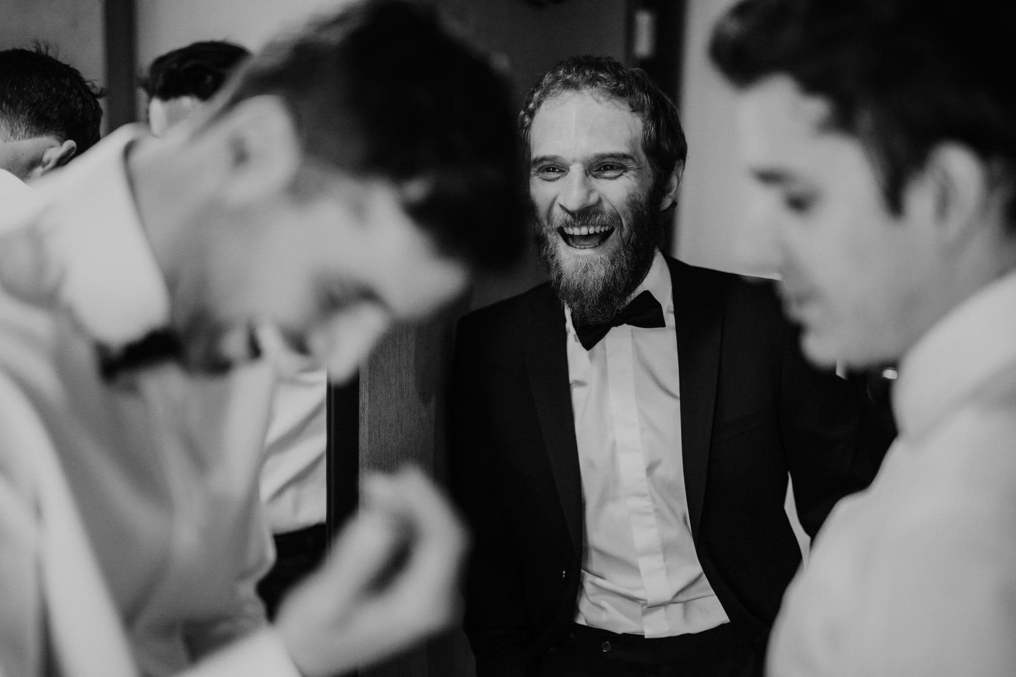 Groomsmen laughing with a suit and bowtie