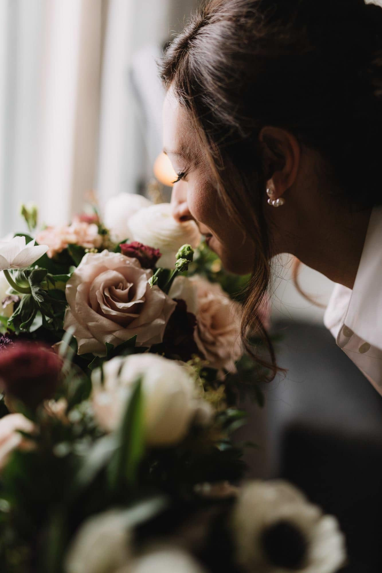 Bride smelling her bouquet for the first time