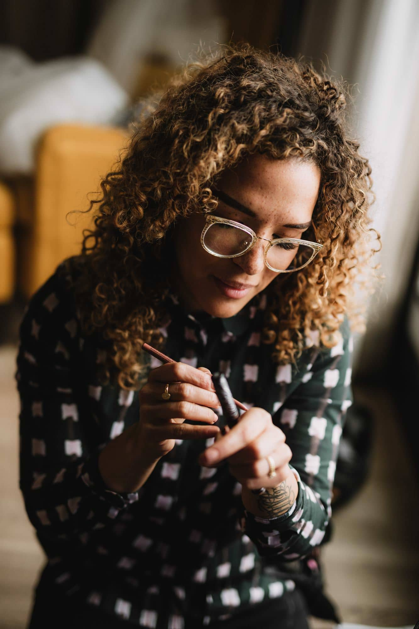 makeup artist with gold curly hair working with her tools