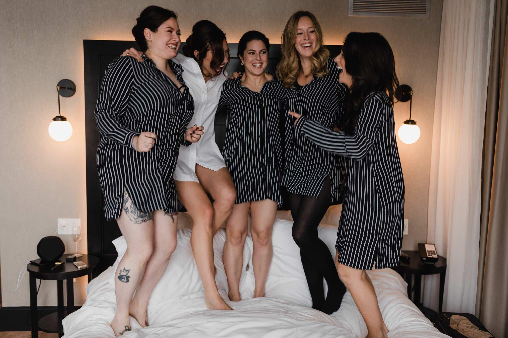 Bridesmaids jump on bed in hotel william grey