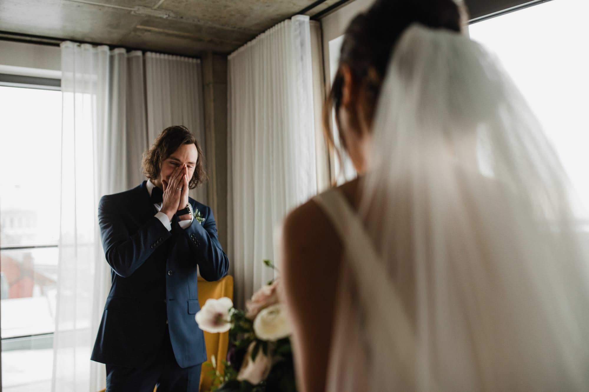 The groom has hands up covering face as he reacts to seeing bride in her dress for the first time