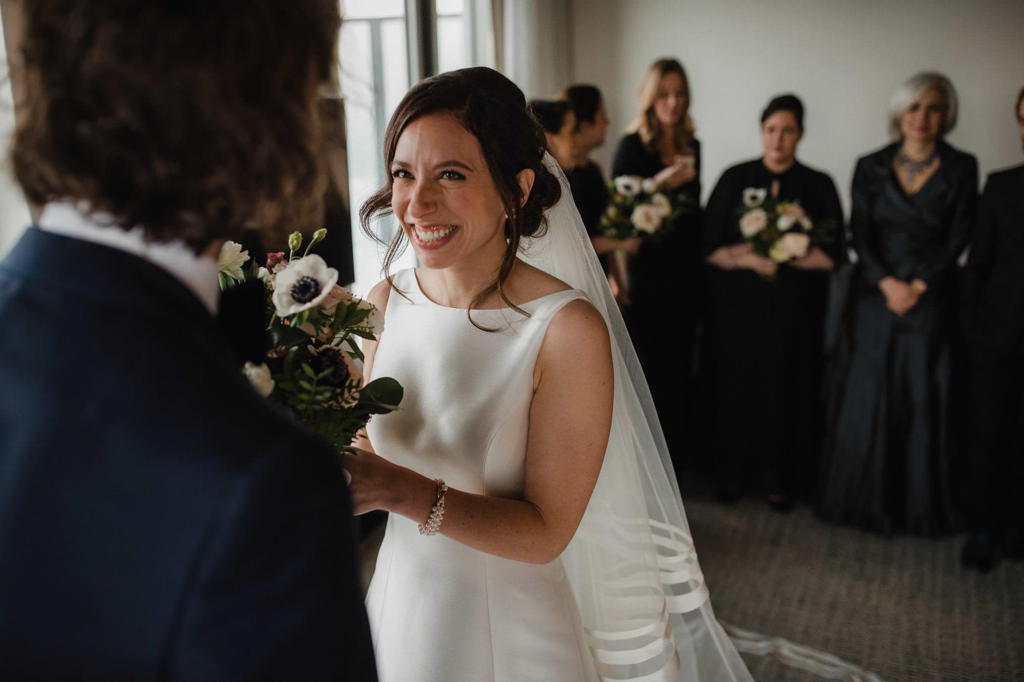 Bride smiles at groom after first look in a hotel room with family in background