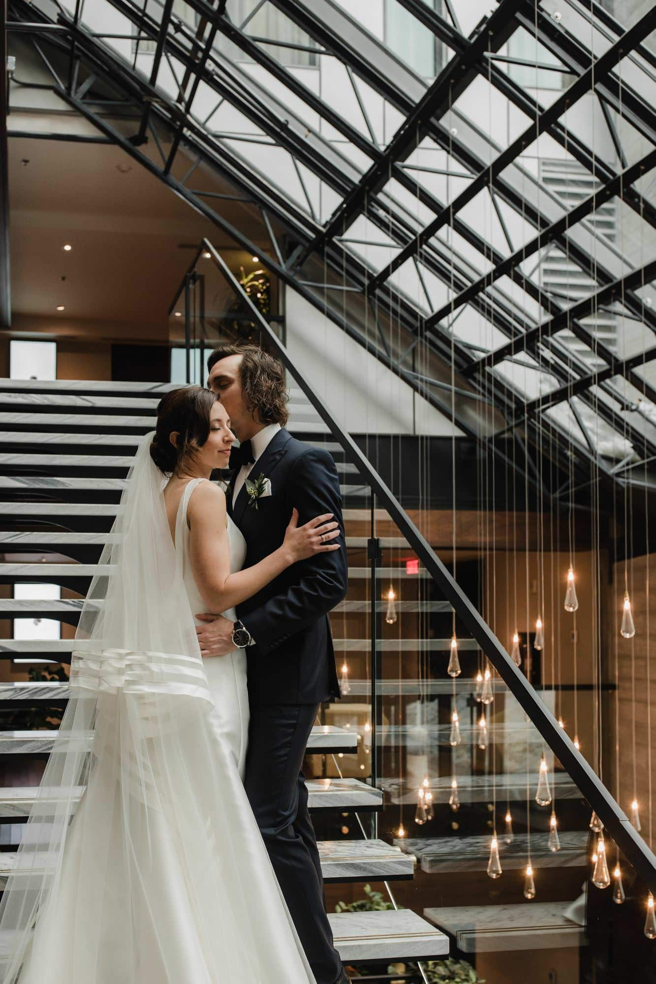 Bride and groom embrace on steps with hanging lights in background in the lobby of Hotel William Grey