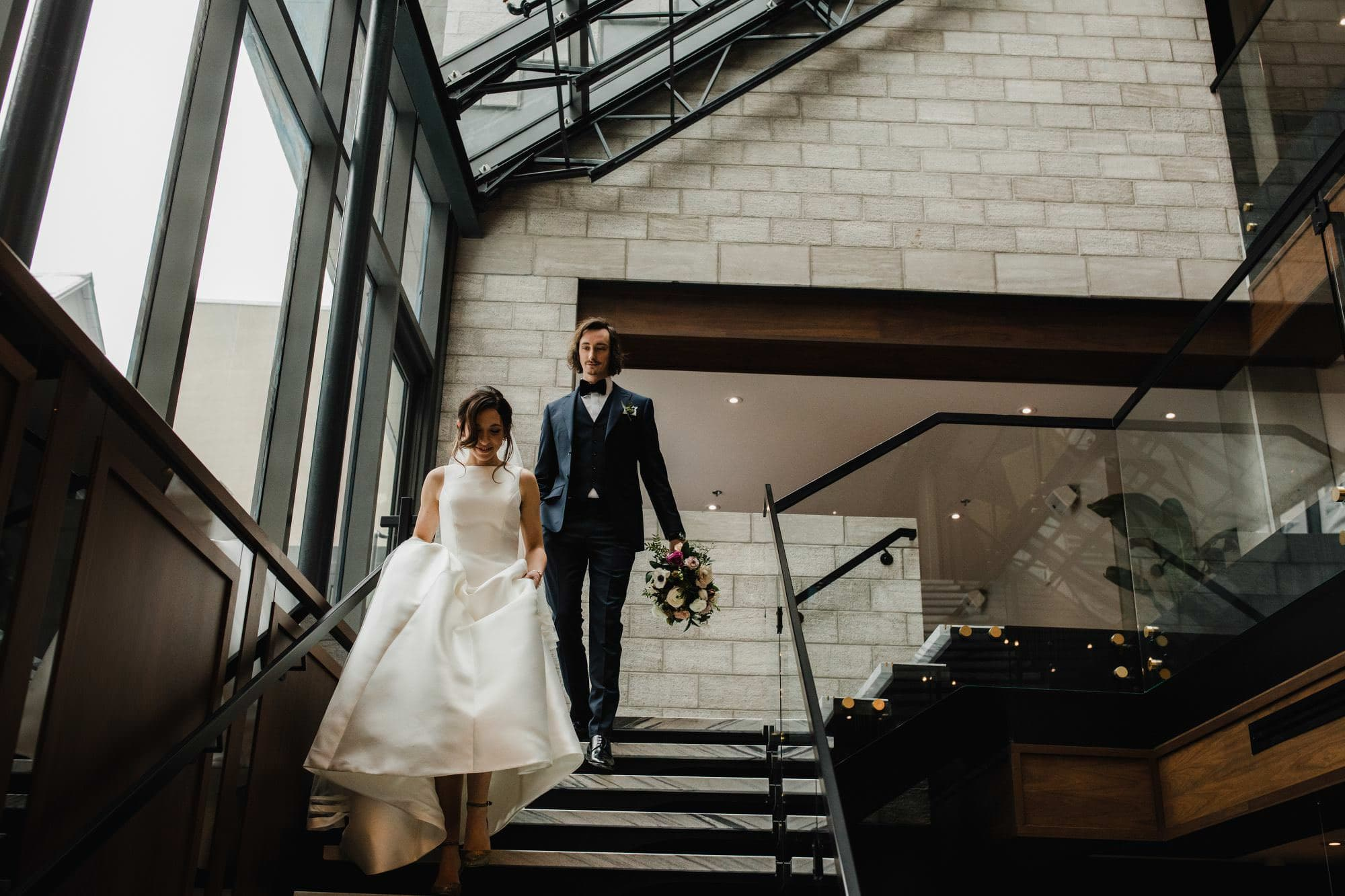 Bride and Groom walk down stairs in the lobby of the william grey hotel with beautiful architecture