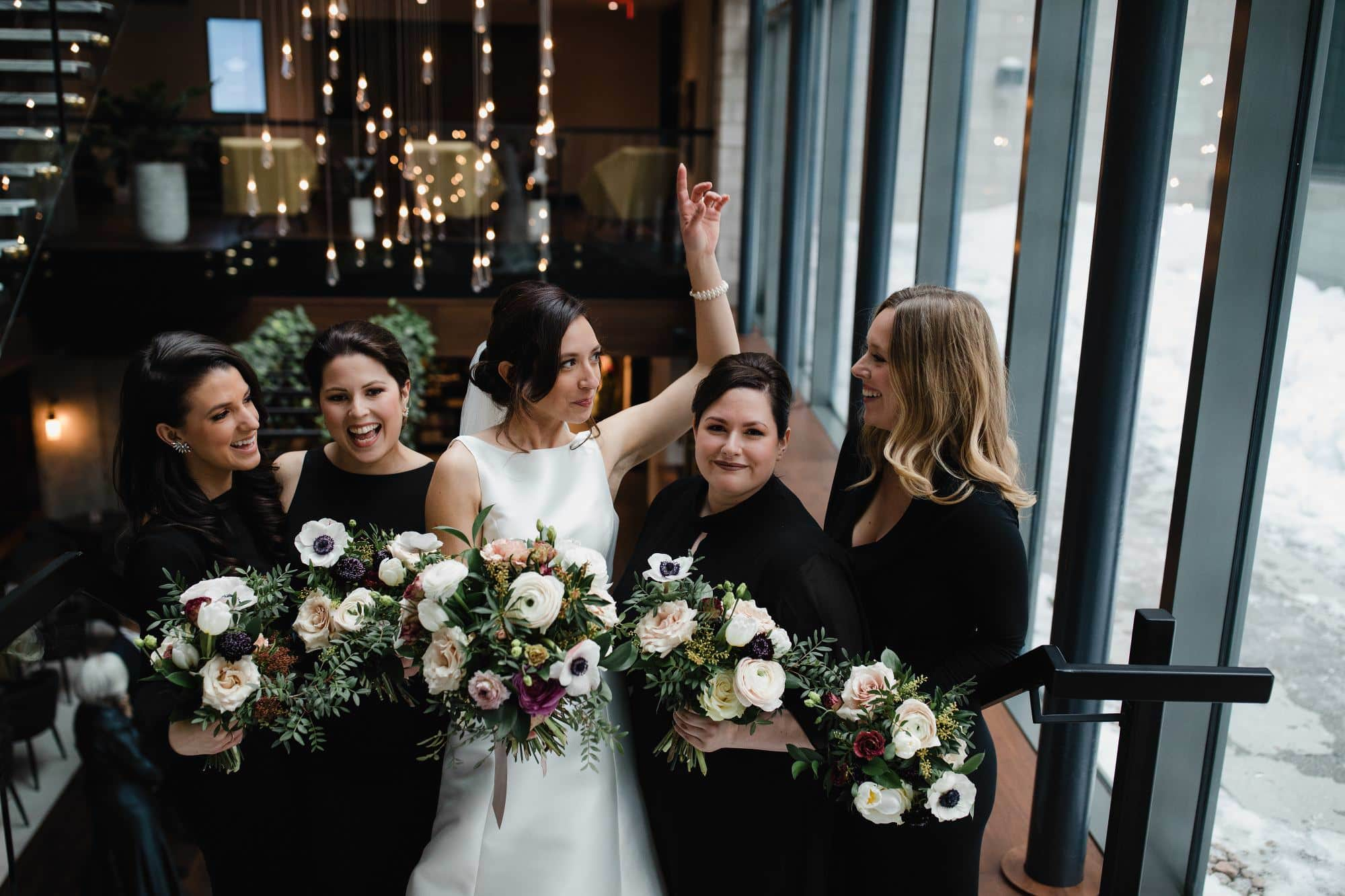 bride with her bridesmaids and their bouquets by Fleuriste astilbe pose in William Grey Hotel lobby