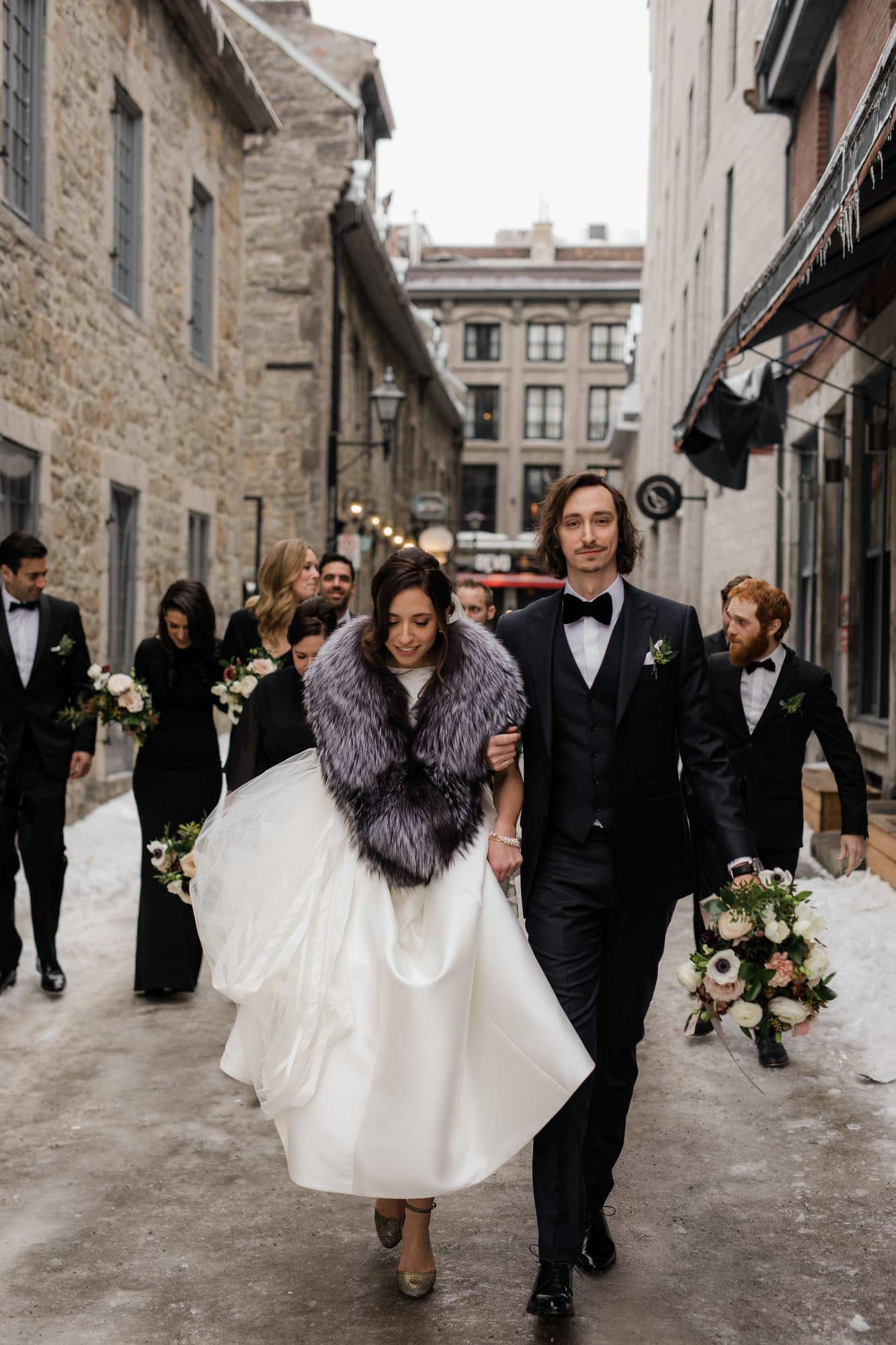 A bride and groom walk on ice outside of the william grey hotel in old montreal
