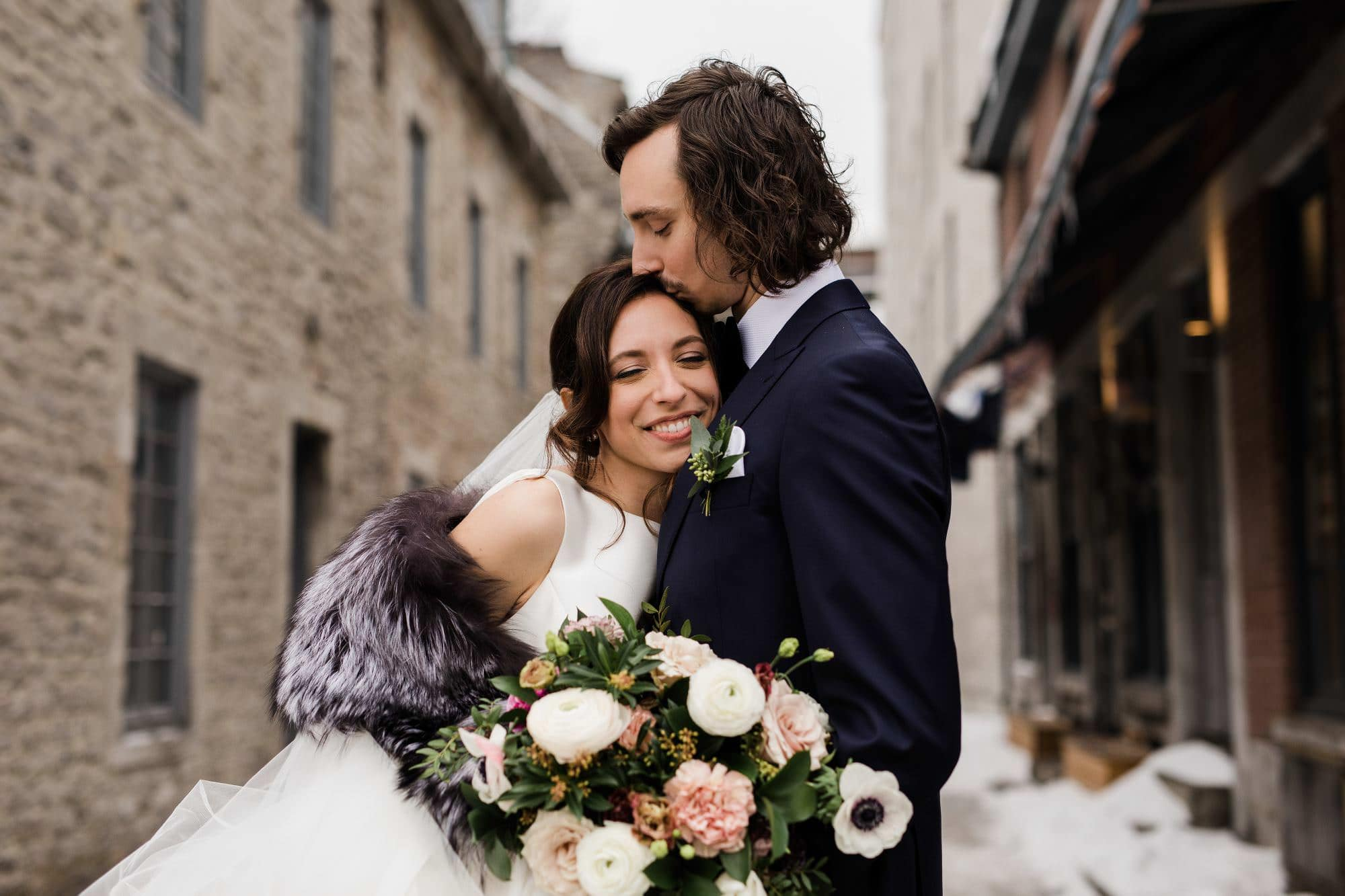 A bride and groom embrace outside of the william grey hotel