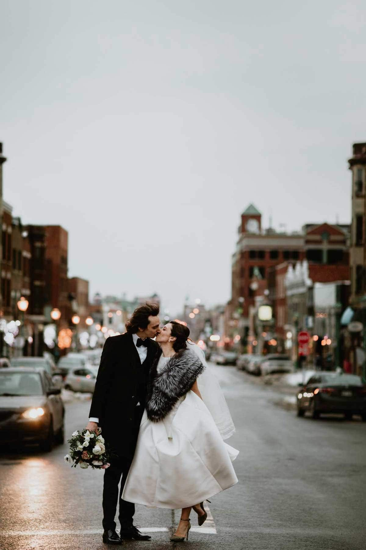 Couple kissing in the middle of a street in Montreal at dusk