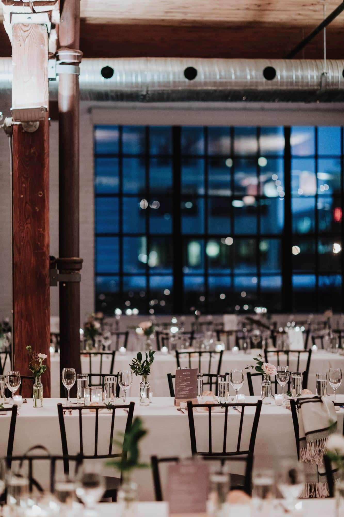 Industrial Wedding With florals on rows of tables with a wooden pillar and sqaured framed glass