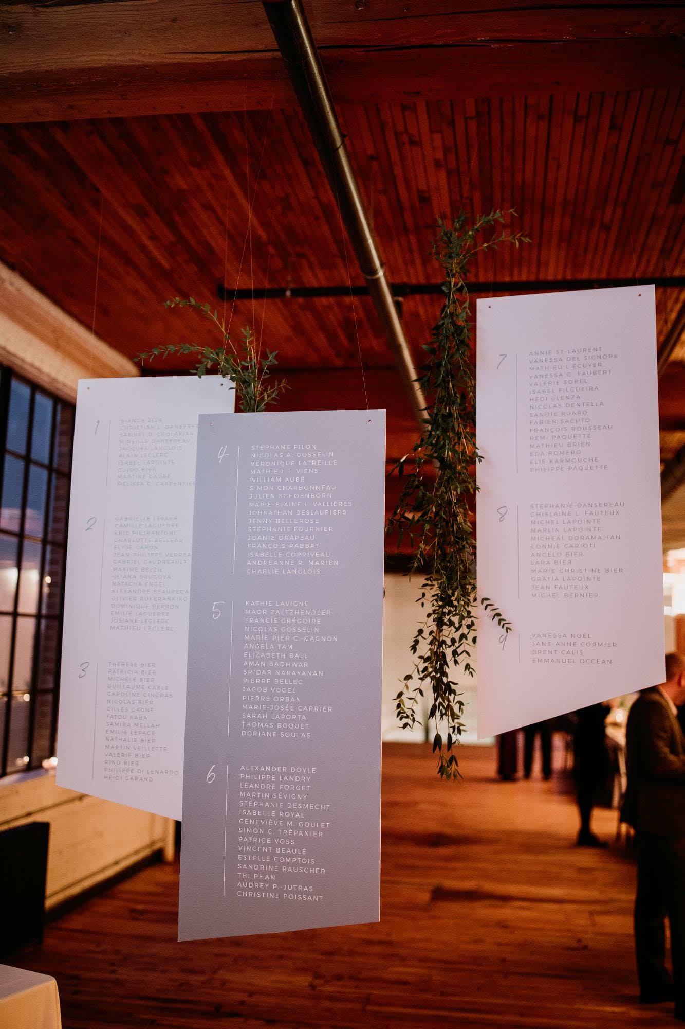 Hanging Seating Charts in a loft for a wedding by White Willow Paper Co