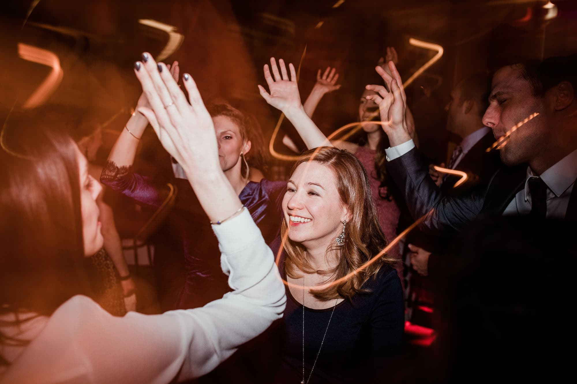 Guest smiling while people dance around her with hands up in the air blurred photo with light streaks