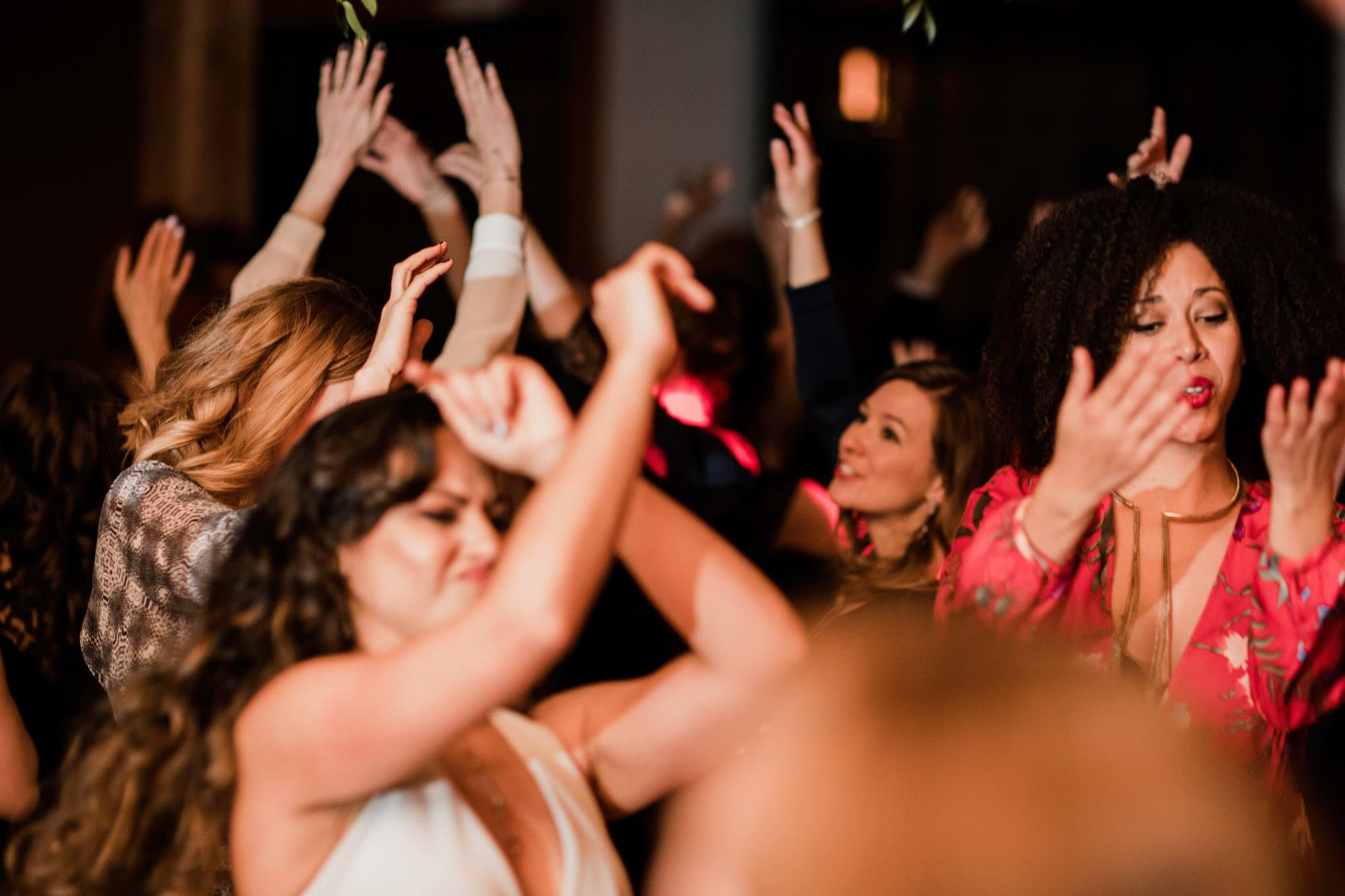 Guests dancing at a wedding with their arms up