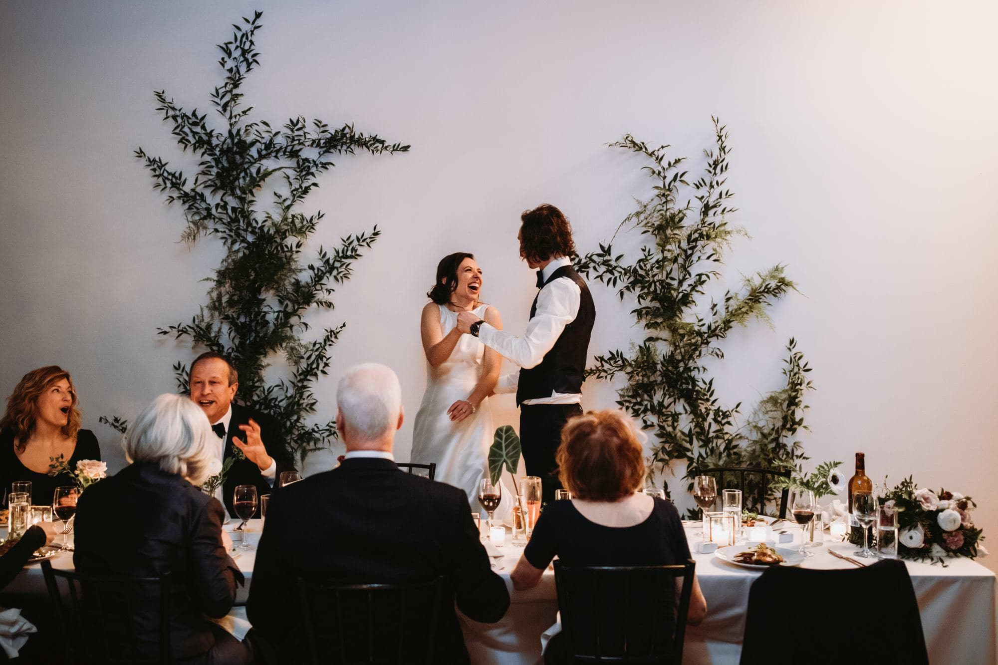 bride and groom talking at head table of wedding