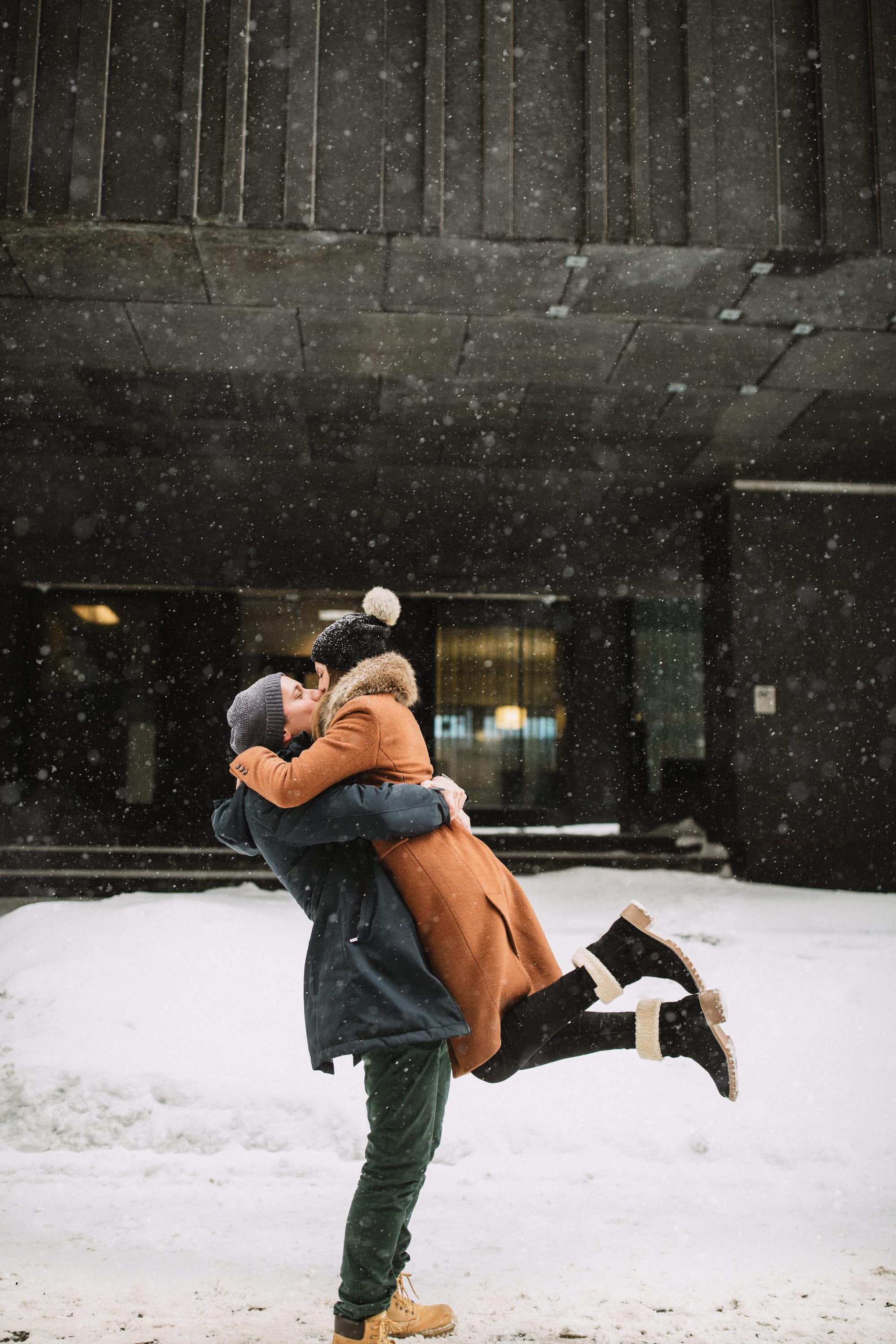A playful embrace during their winter engagement session near rue notre dame in vieux port Montreal with Montreal photographer Brent Calis.