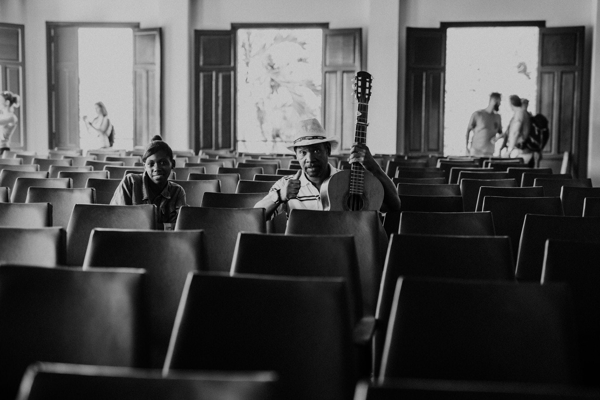 Black and white photo of patrons at the local concert hall in Vinales, Cuba. Wedding and travel photographer Brent Calis.