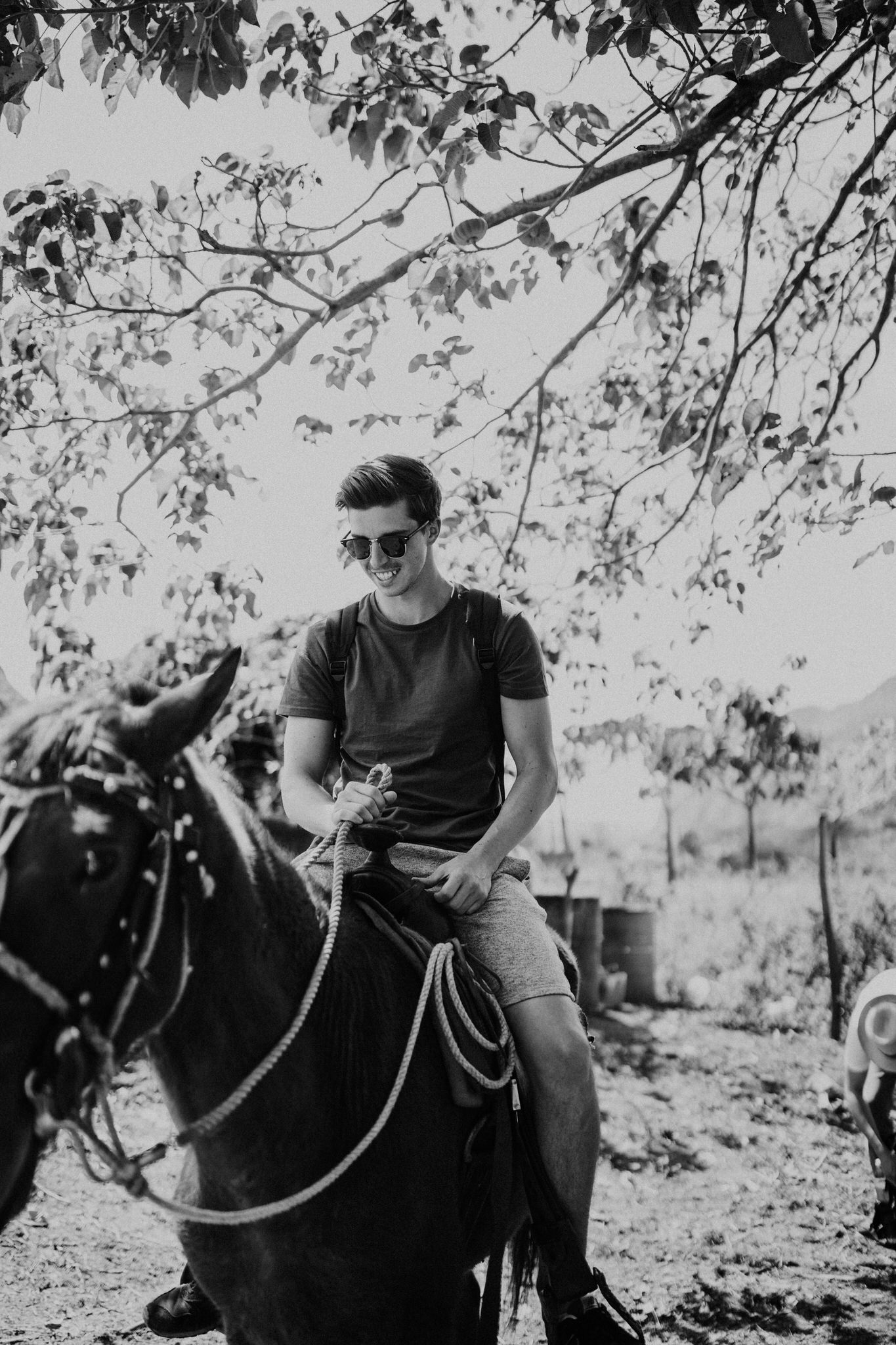 Black and white portrait on horseback through the cigar farm in Vinales, Cuba. Wedding and travel photographer Brent Calis.