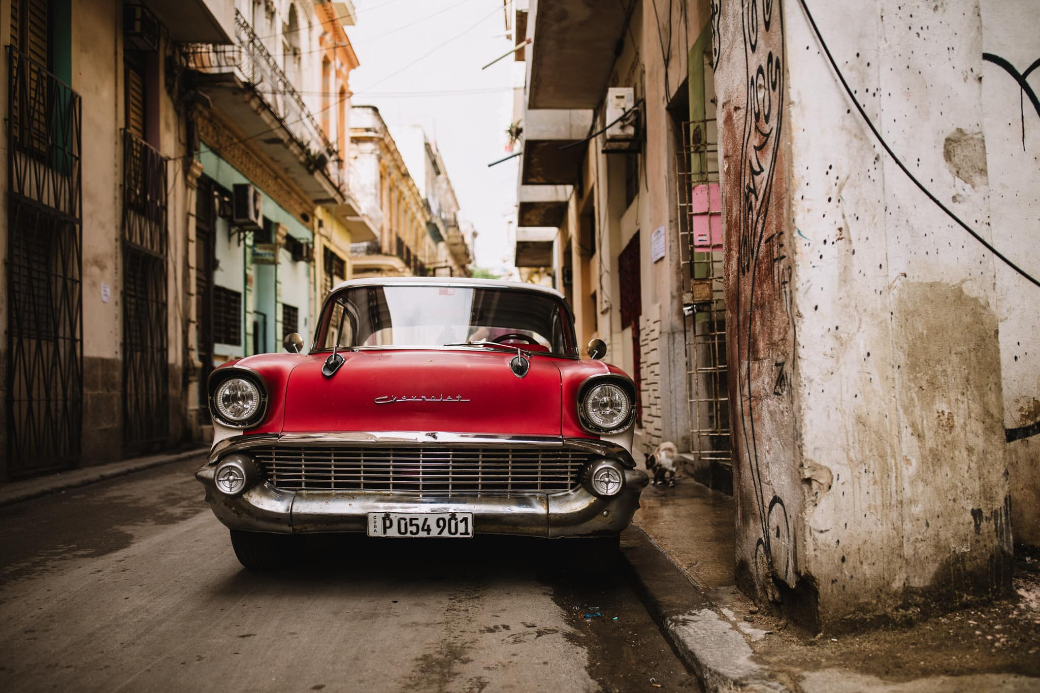 A red Chevrolet, one of the classic cars of cuba, near the Malecon in Havana. Travel photographer Brent Calis.