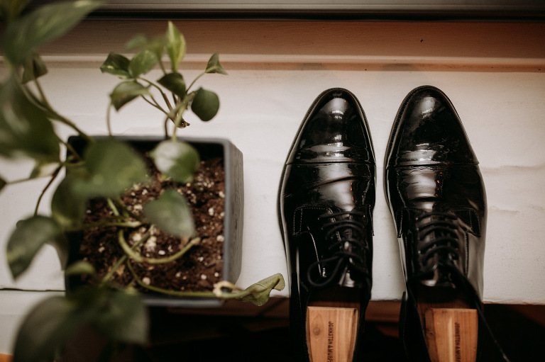 Black dress shoes and plant in window. Wedding Photographer Brent Calis.