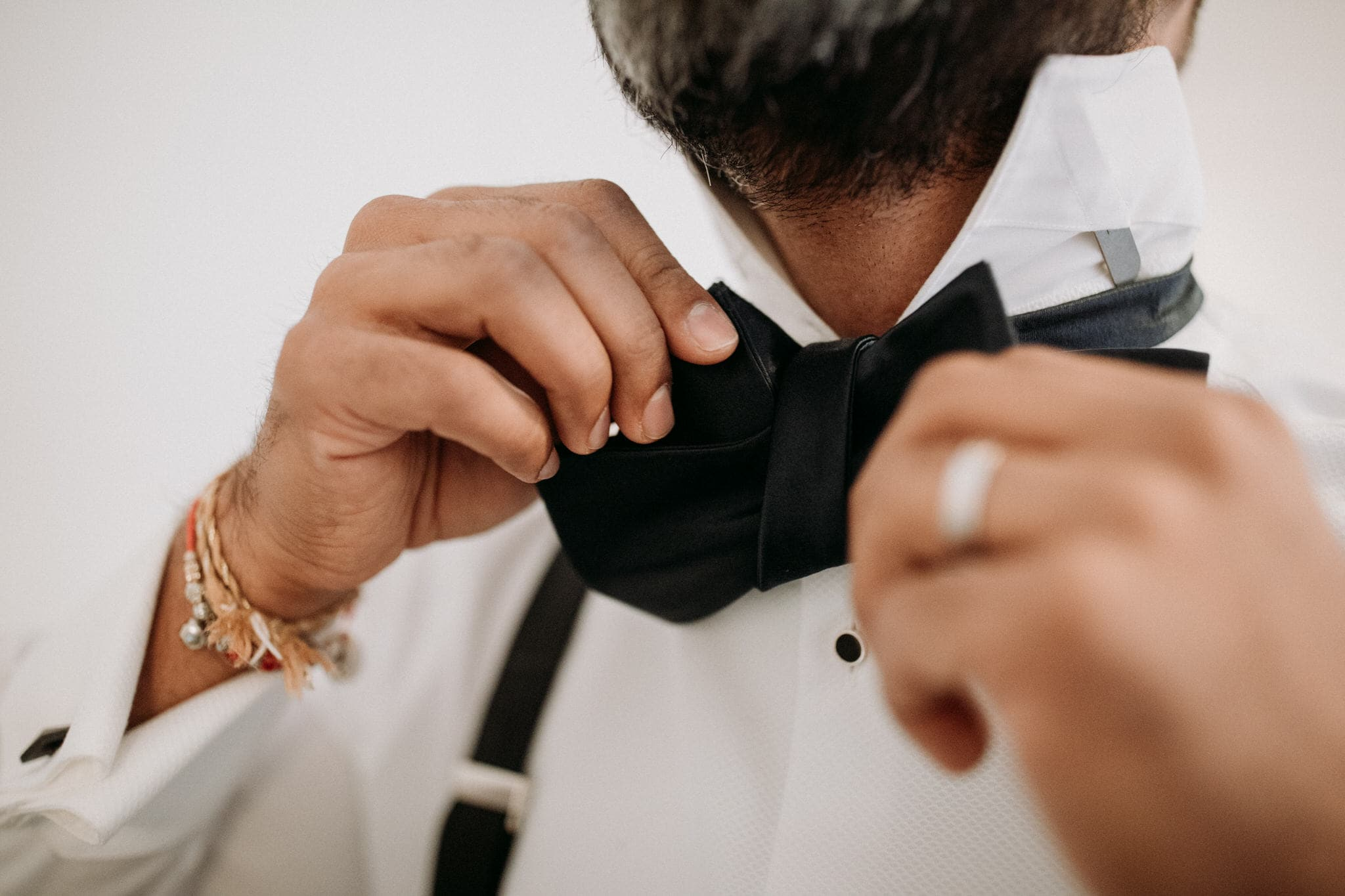 The groom adjusts his bowtie. Wedding Photographer Brent Calis.