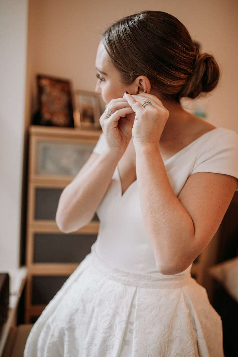 The bride puts on her earrings. Wedding Photographer Brent Calis.