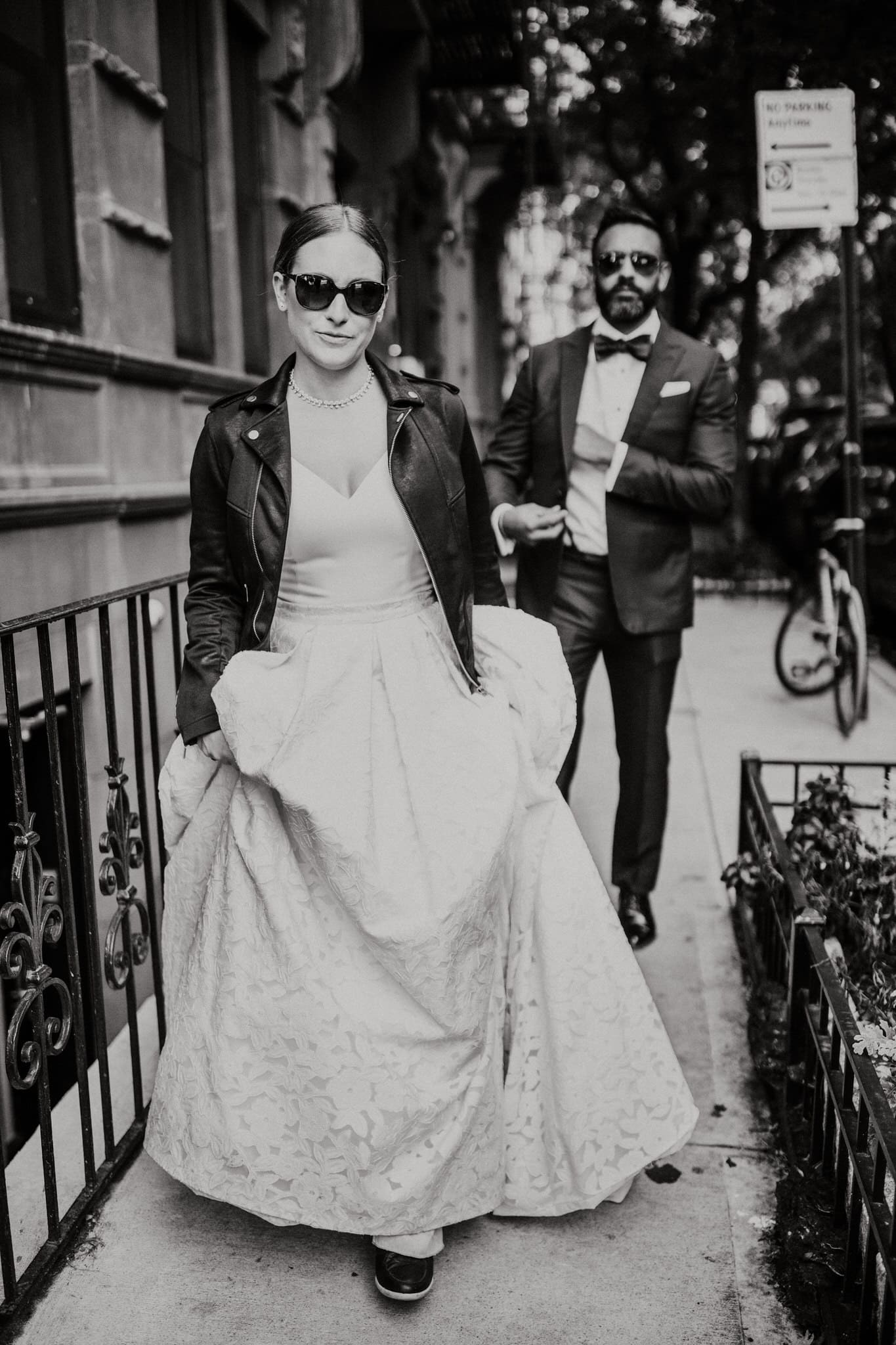 Black and white portrait of the bride and groom in sunglasses and a leather jacket as they begin their walk through the streets of New York. Wedding Photographer Brent Calis.