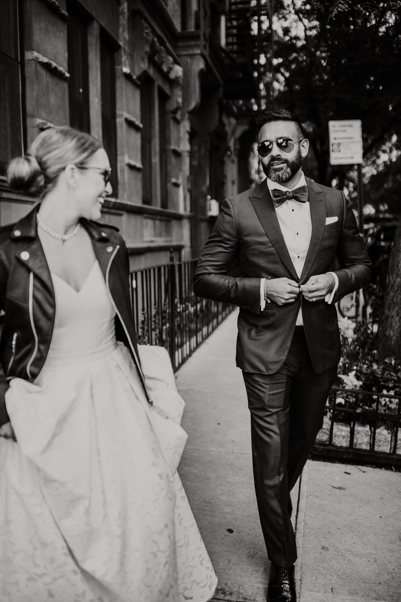 Black and white portrait of the groom in sunglasses adjusting his jacket as they begin their walk through the streets of New York. Wedding Photographer Brent Calis.