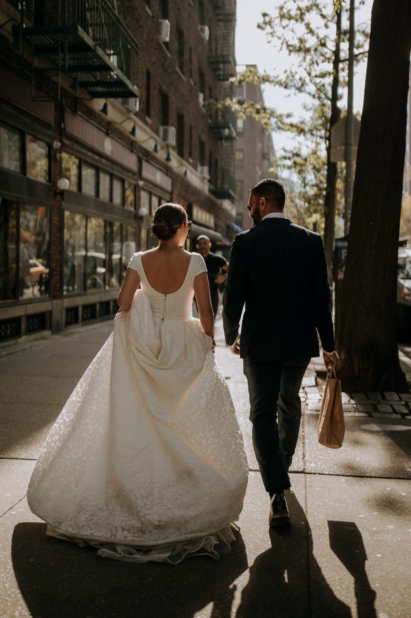 The bride and groom walk through the streets of New York. Wedding Photographer Brent Calis.