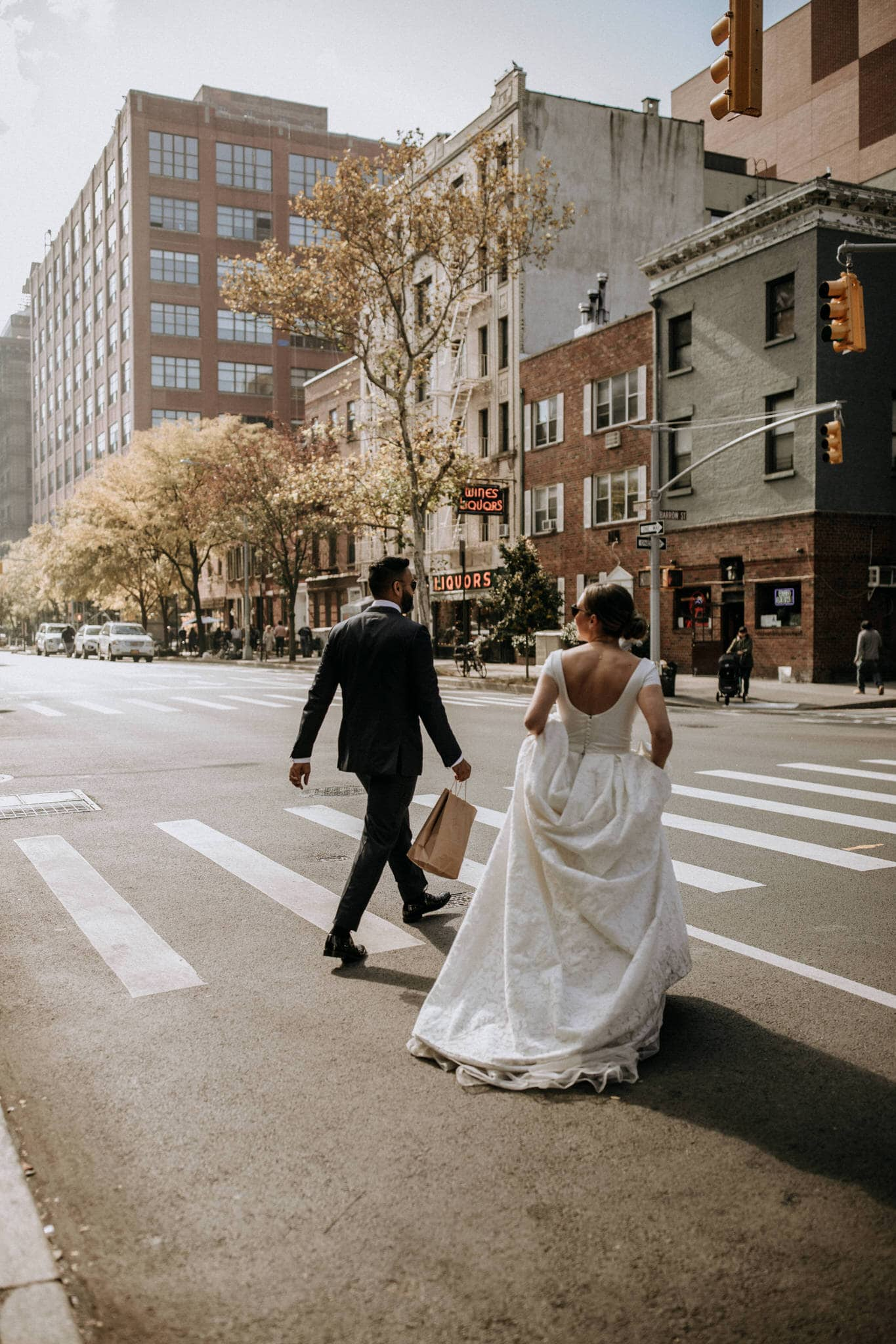 The bride and groom cross the steet on their walk through the streets of New York. Wedding Photographer Brent Calis.