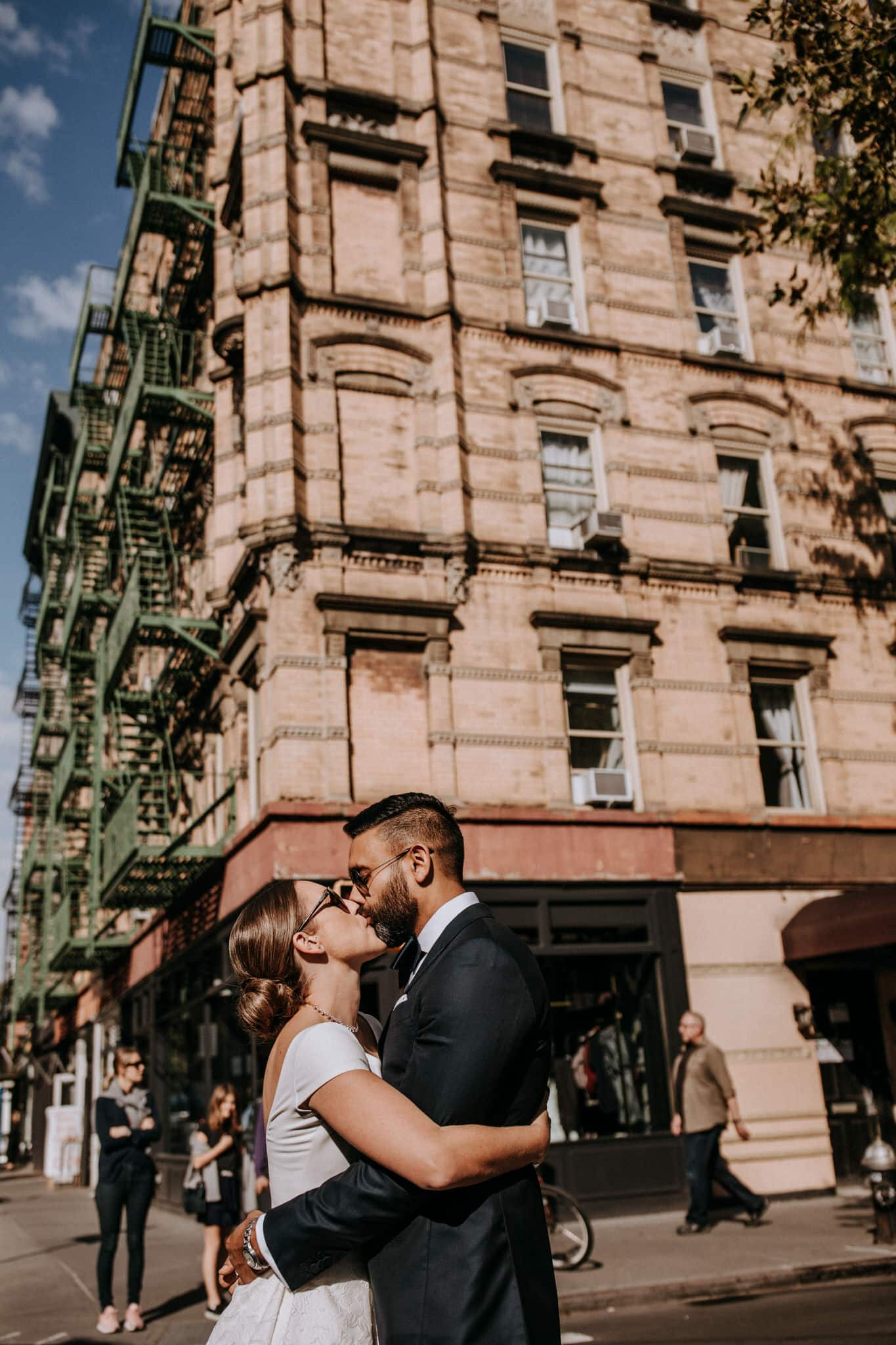 The bride and groom kissing on their walk through the streets of New York. Wedding Photographer Brent Calis.