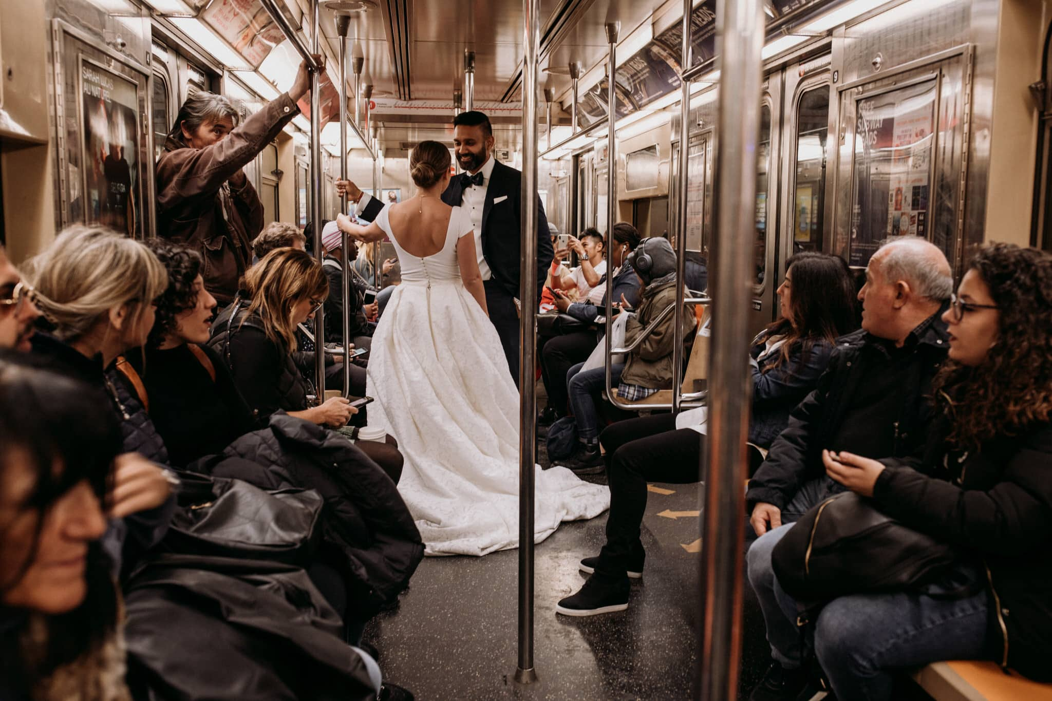 The bride and groom ride the subway in New York City. Wedding Photographer Brent Calis.