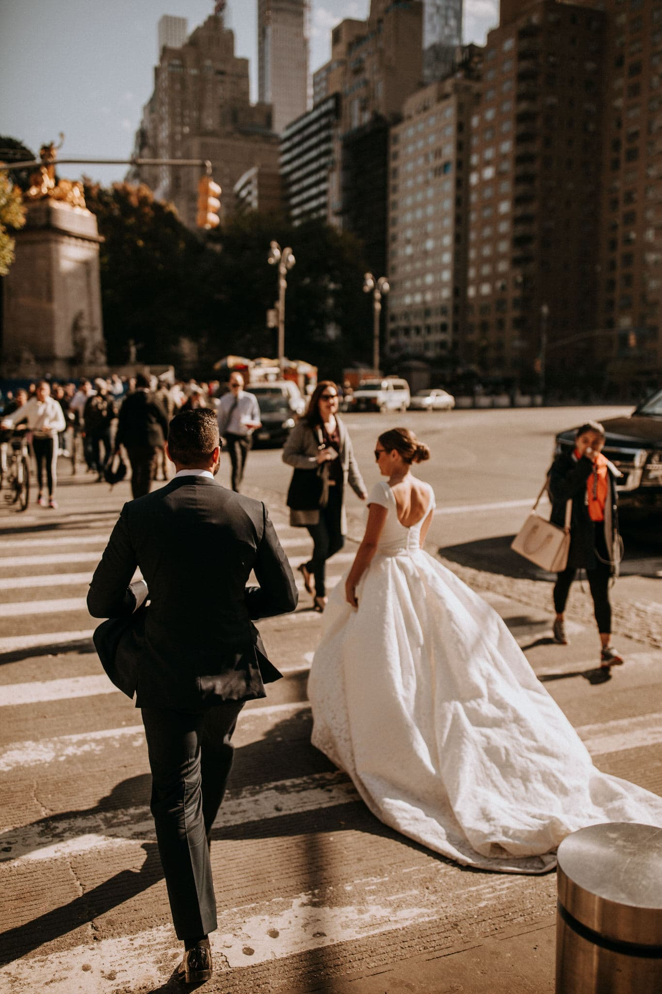 The bride and groom cross the steet to Central Park on their walk through the streets of New York. Wedding Photographer Brent Calis.
