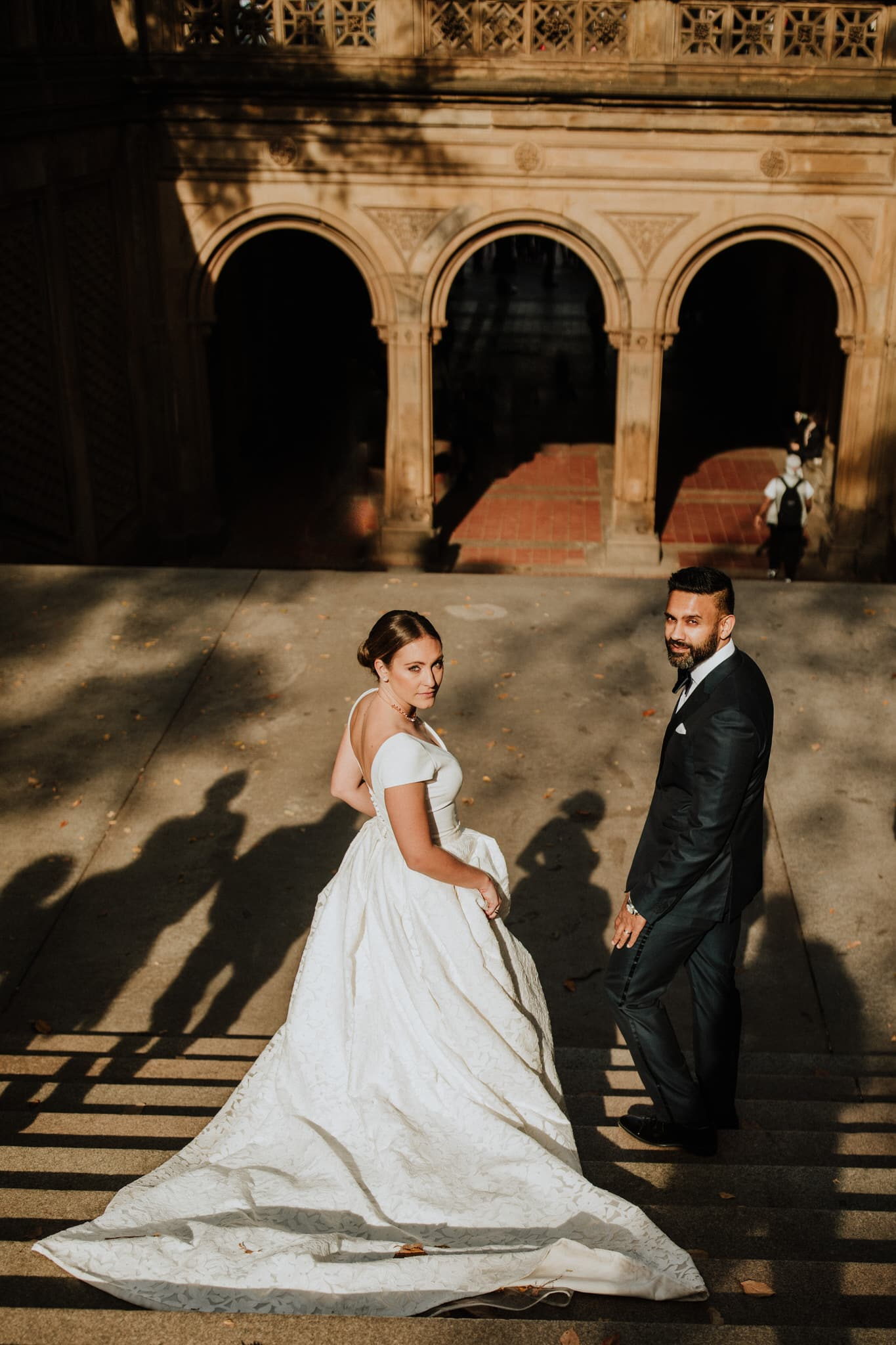 The bride and groom walk down the stairs in Central Park, New York City. Wedding Photographer Brent Calis.
