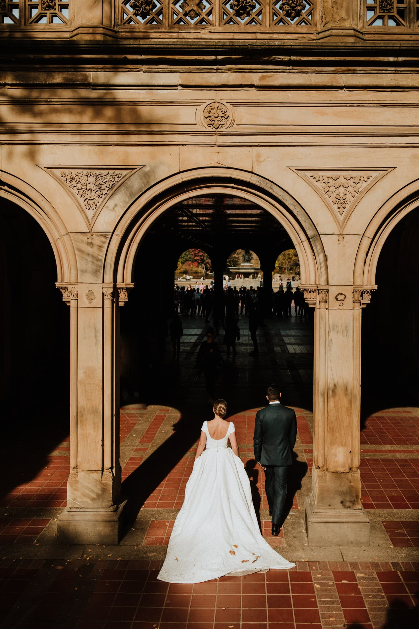 The bride and groom walk under the archway towards Bethesda Terrace in Central Park, New York City. Wedding Photographer Brent Calis.