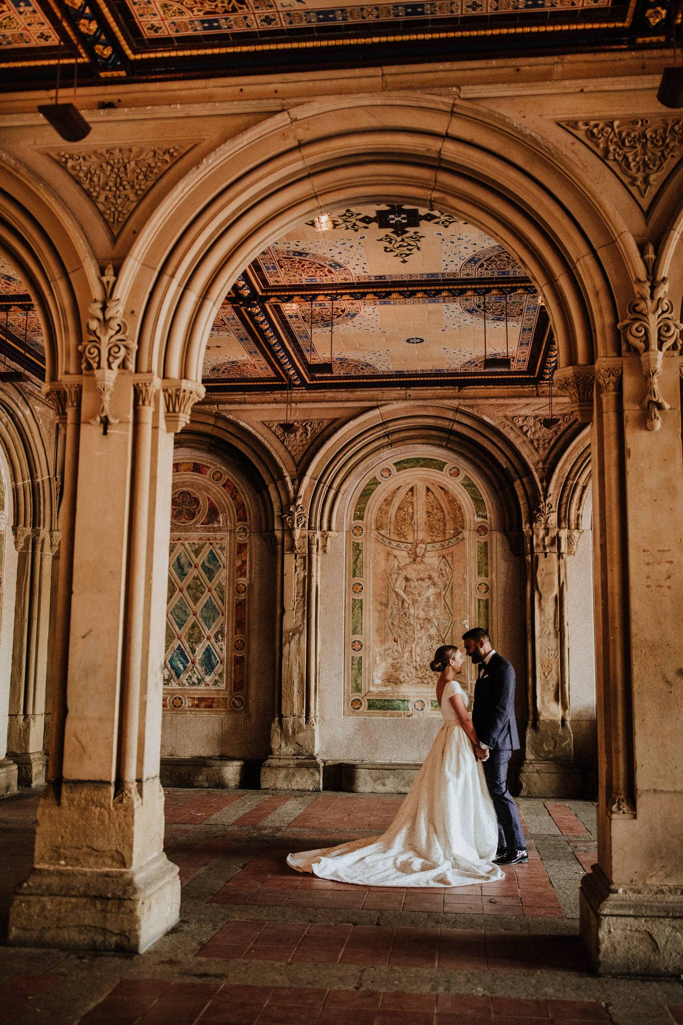 The bride and groom embrace under the Bethesda Terrace in Central Park, New York City. Wedding Photographer Brent Calis.