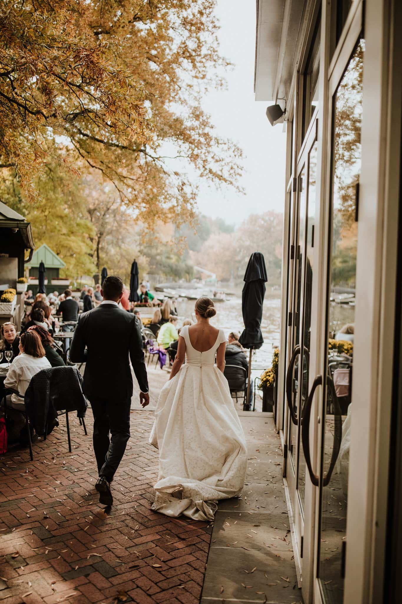 The bride and groom walk through Tavern on the Green in Central Park, New York City. Wedding Photographer Brent Calis.