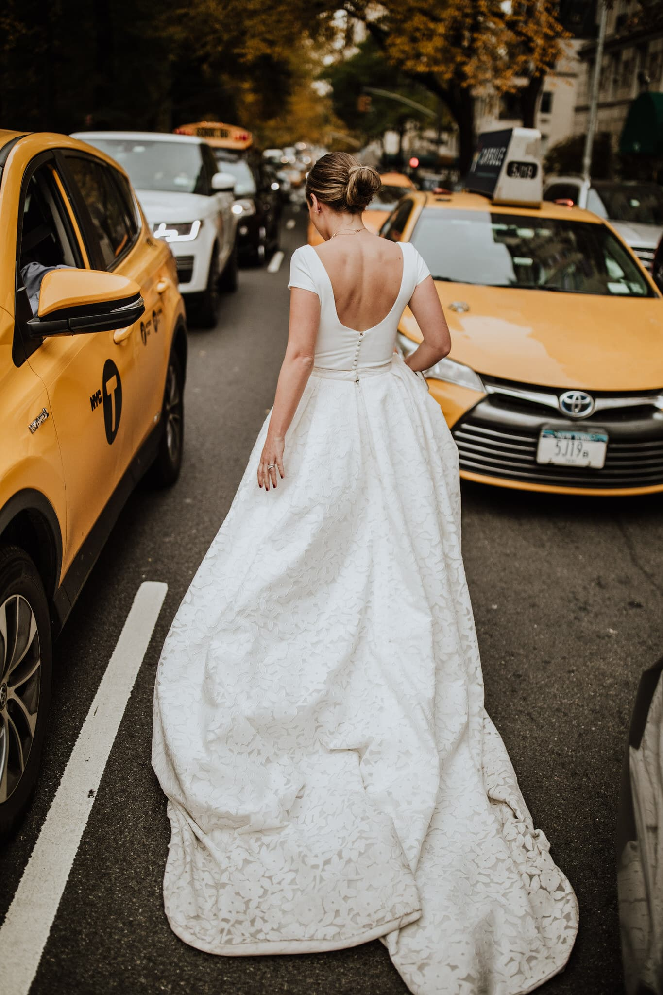The bride catches a taxi near Central Park, New York City. Wedding Photographer Brent Calis.