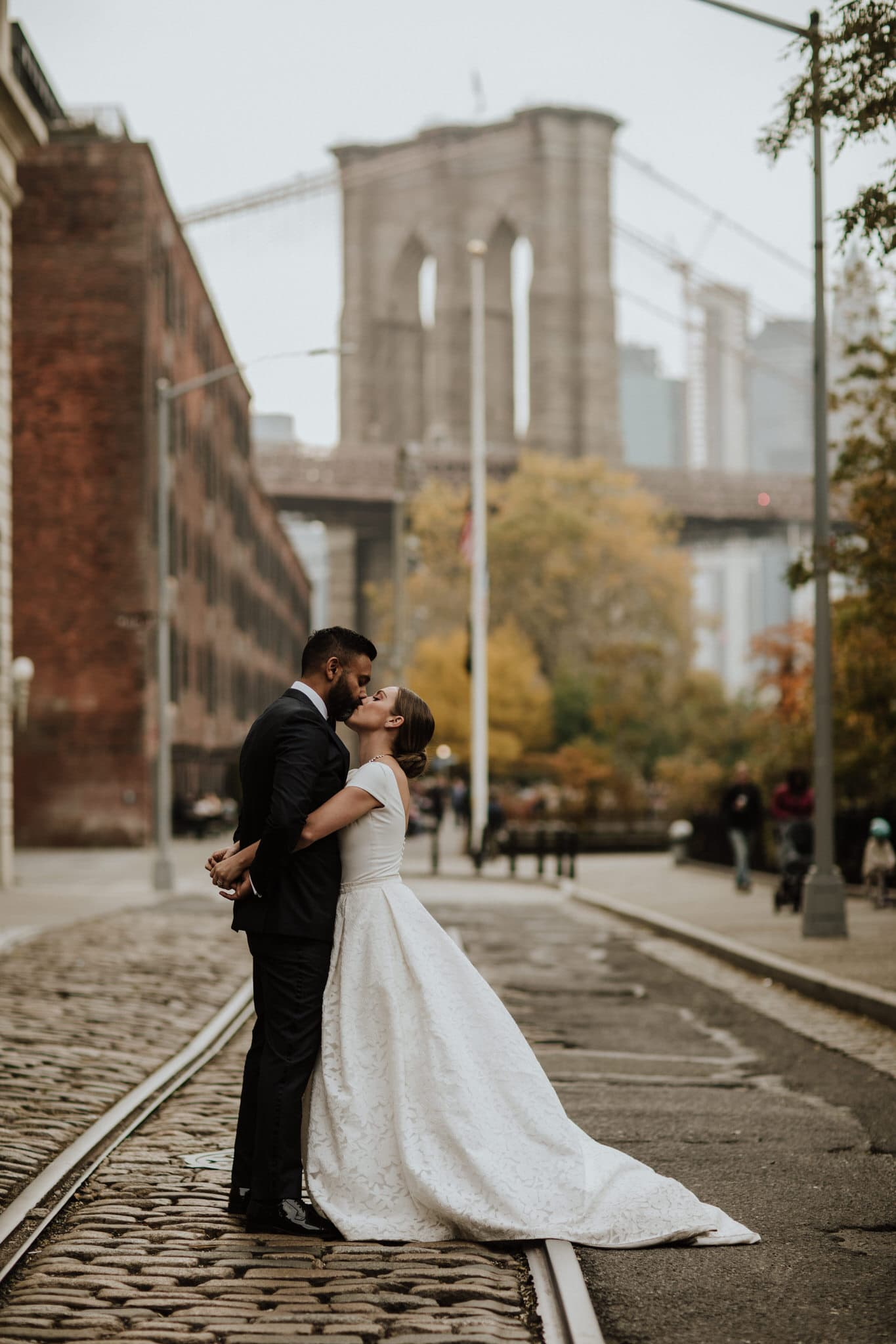 The bride and groom kiss on the cobble stones streets of Brooklyn, New York. Wedding Photographer Brent Calis.