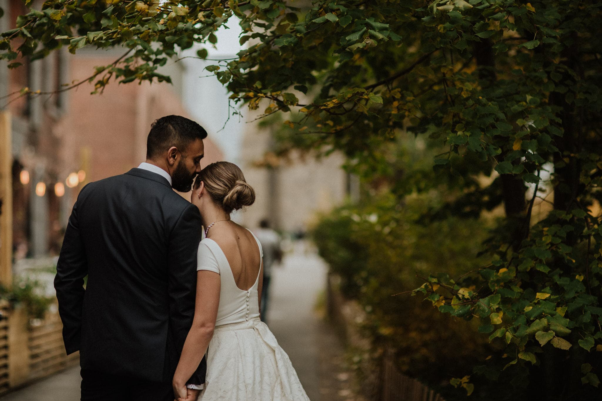 The bride and groom share a moment under the trees in Brooklyn, New York. Wedding Photographer Brent Calis.