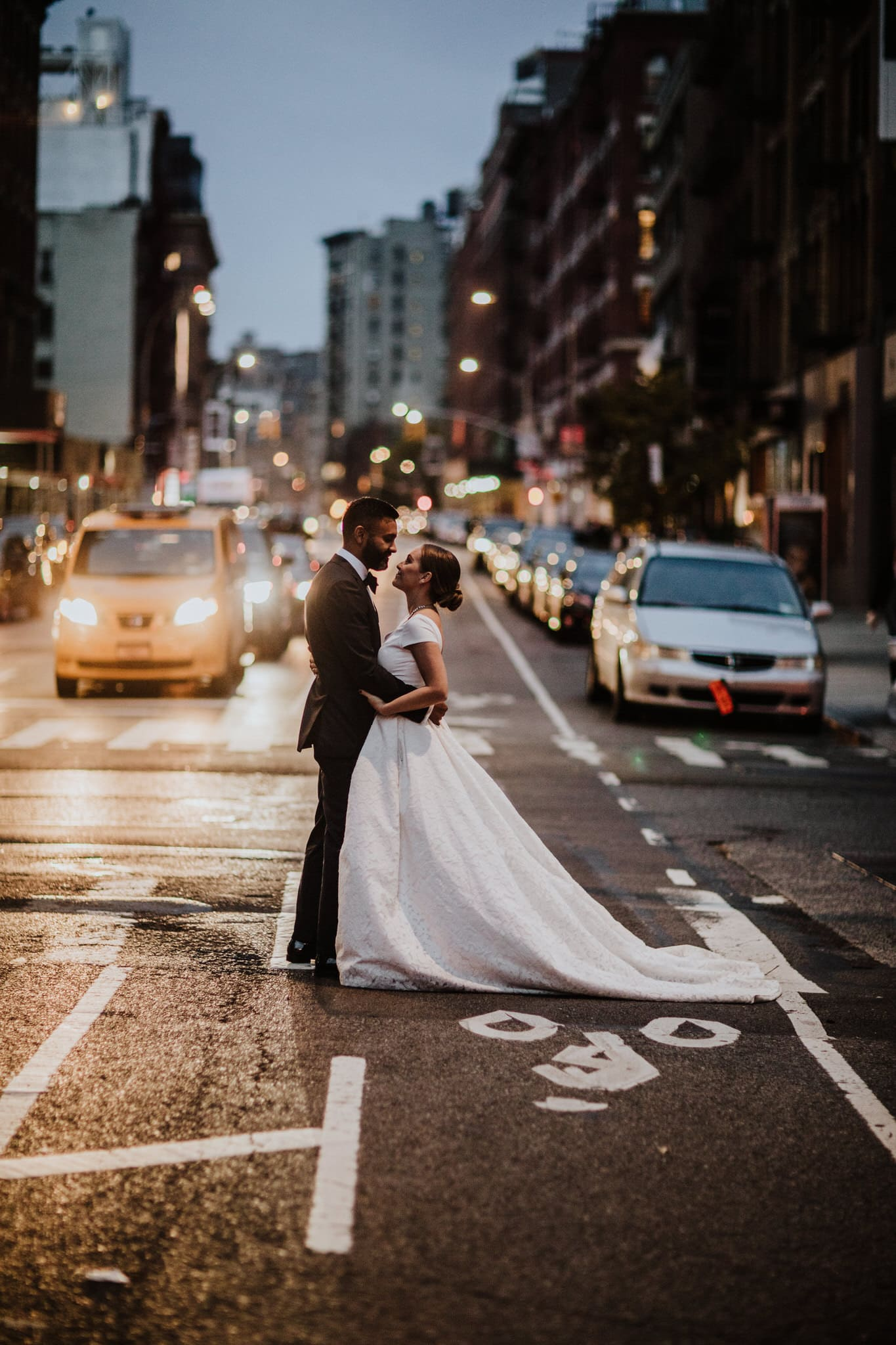 The bride and groom pose in the streets of New York at dusk. Wedding Photographer Brent Calis.