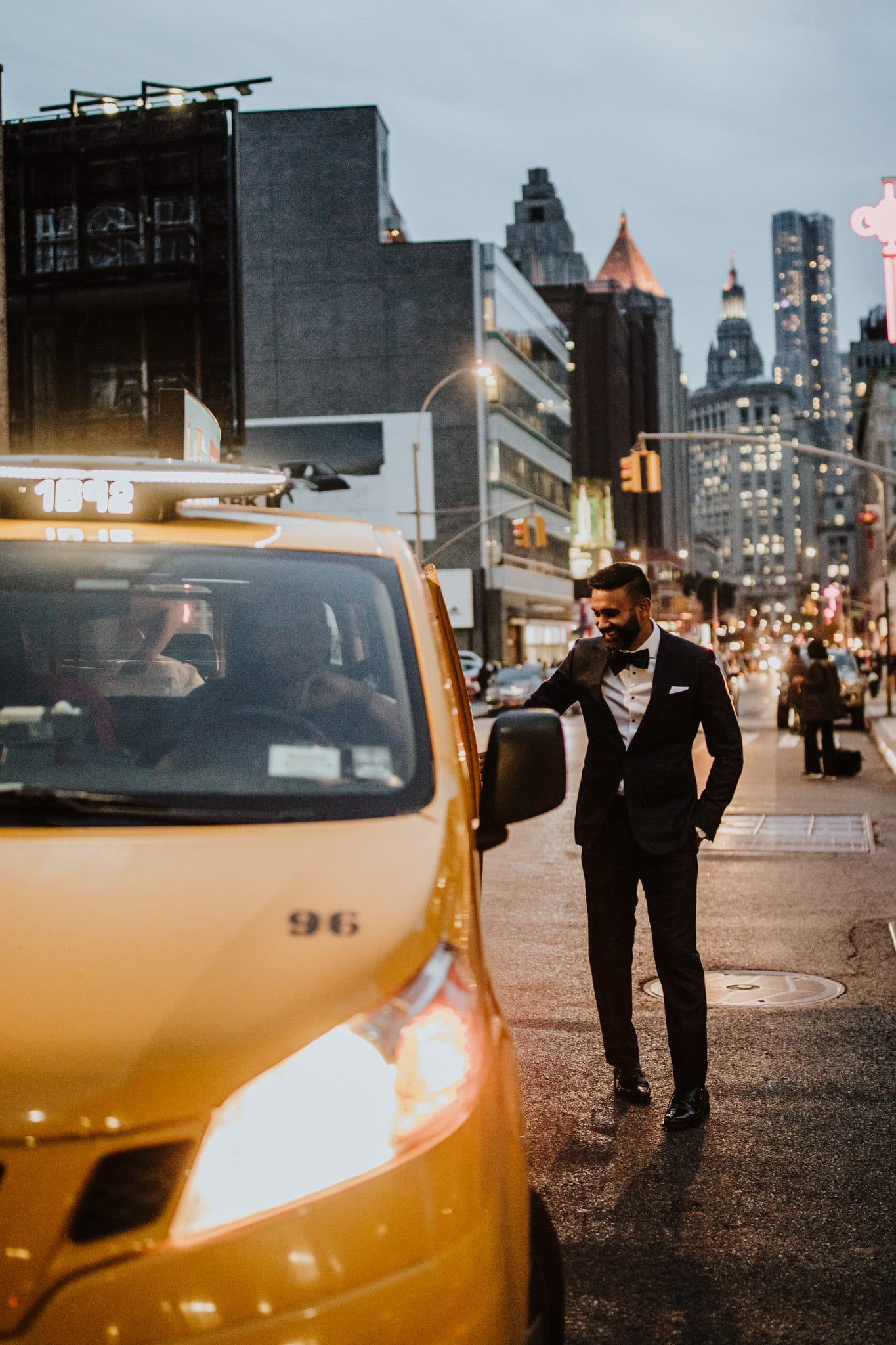 The bride and groom catch a taxi in New York at dusk. Wedding Photographer Brent Calis.