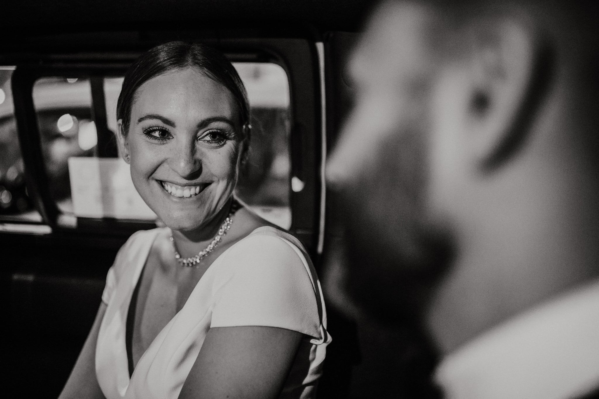 Black and white photo as the bride smiles at her groom in the taxi. Wedding Photographer Brent Calis.