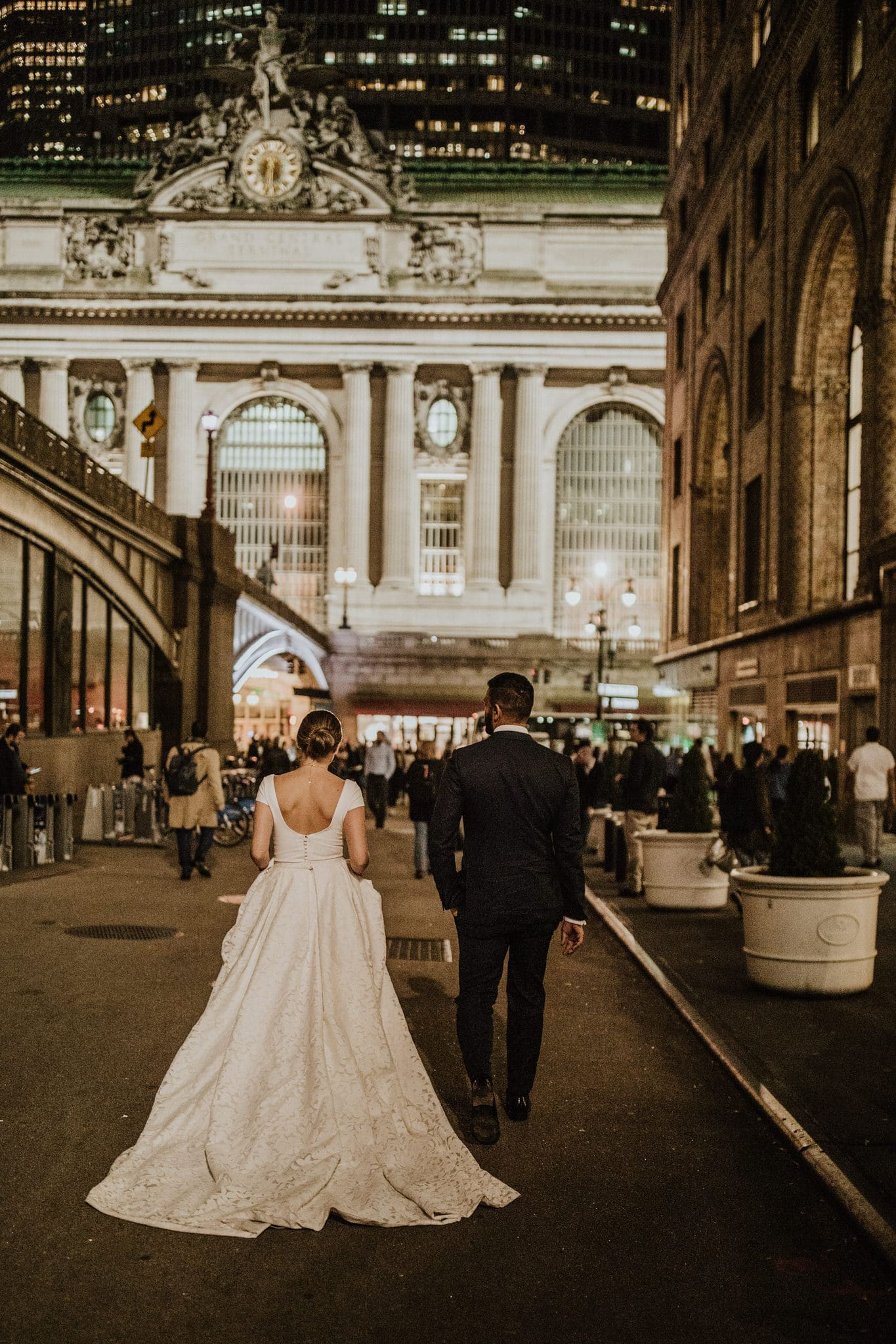 The bride and groom walk towards New York's Central Station. Wedding Photographer Brent Calis.