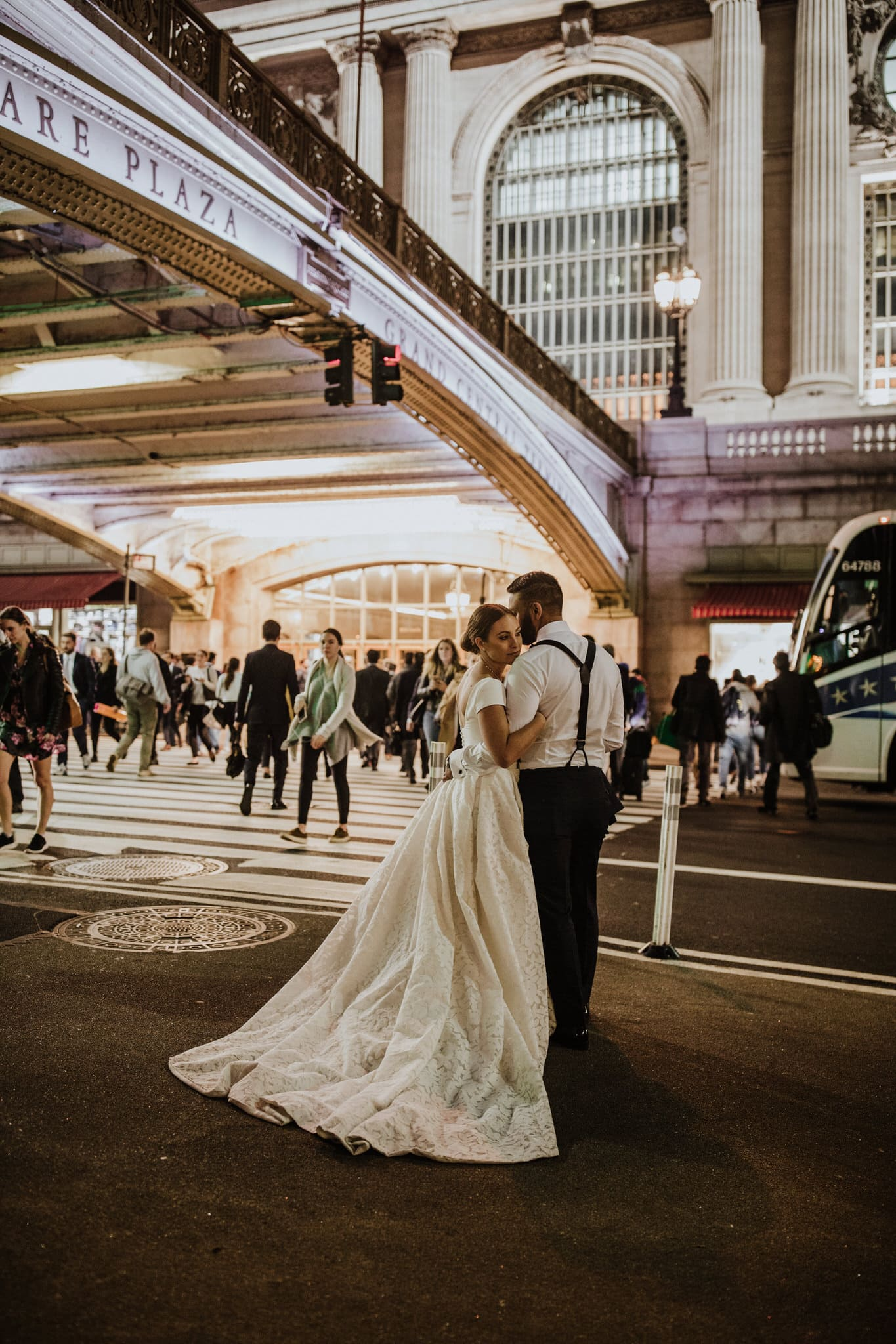 The bride and groom embrace in front of Central Station, New York. Wedding Photographer Brent Calis.
