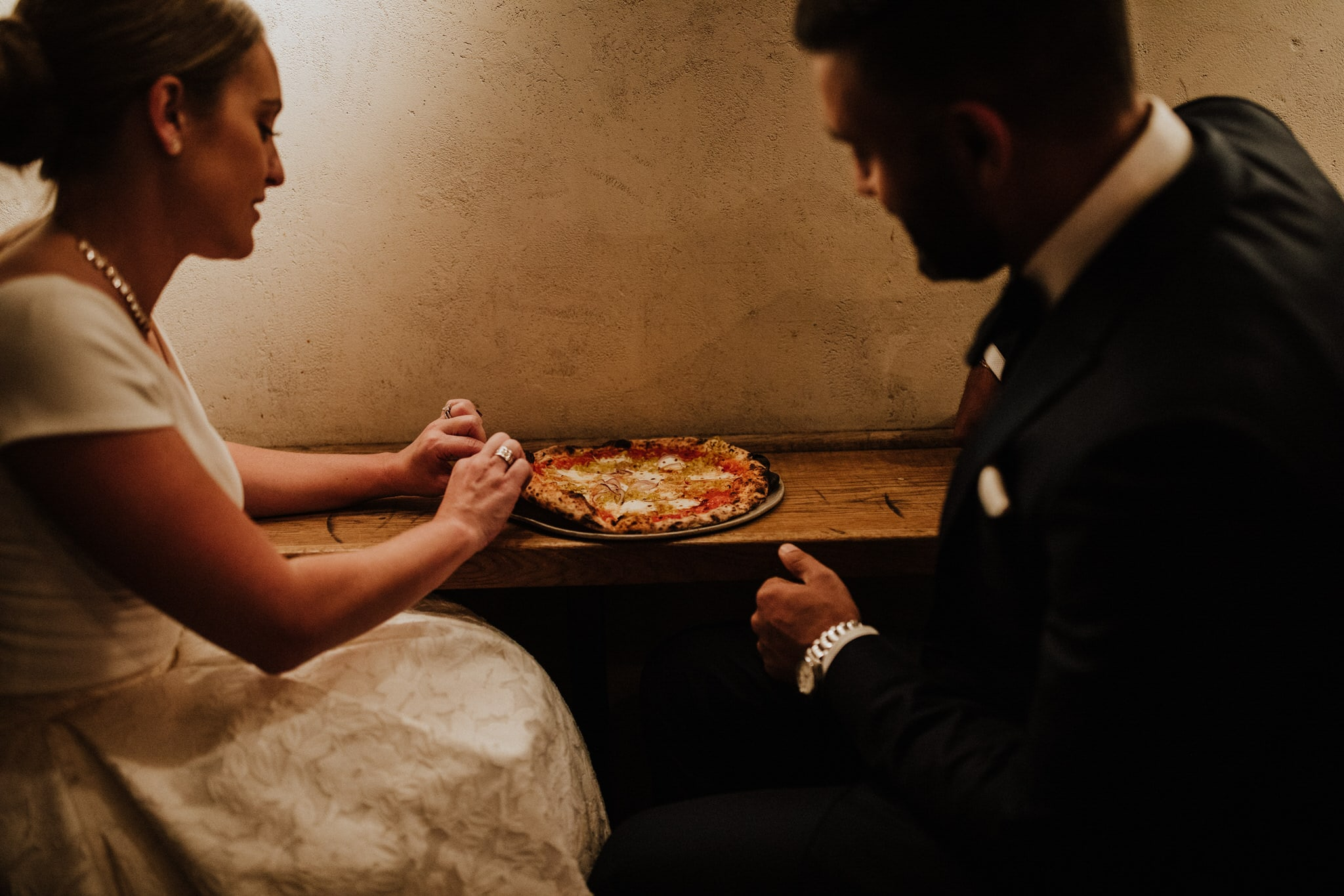 The bride and groom share Roberta's Pizza in New York City. Wedding Photographer Brent Calis.
