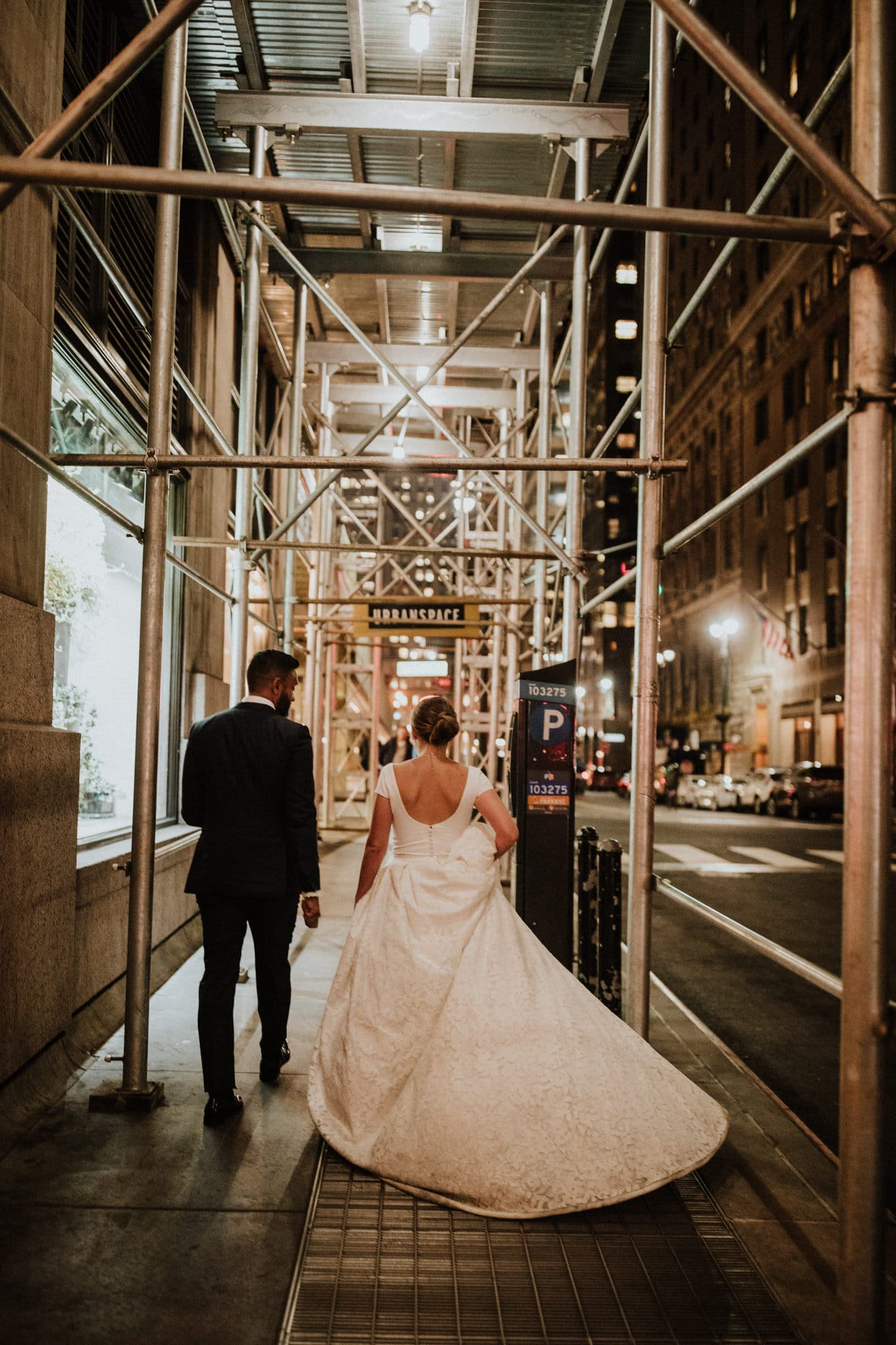 The bride and groom walk the city streets of New York at night. Wedding Photographer Brent Calis.