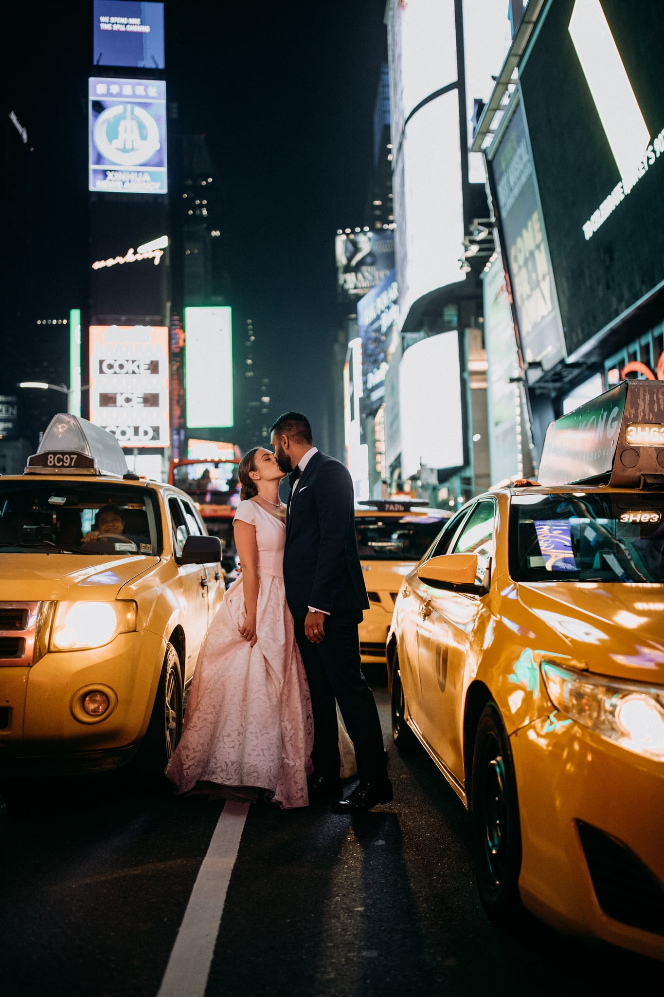 The bride and groom kiss at Times Square in New York City. Wedding Photographer Brent Calis.