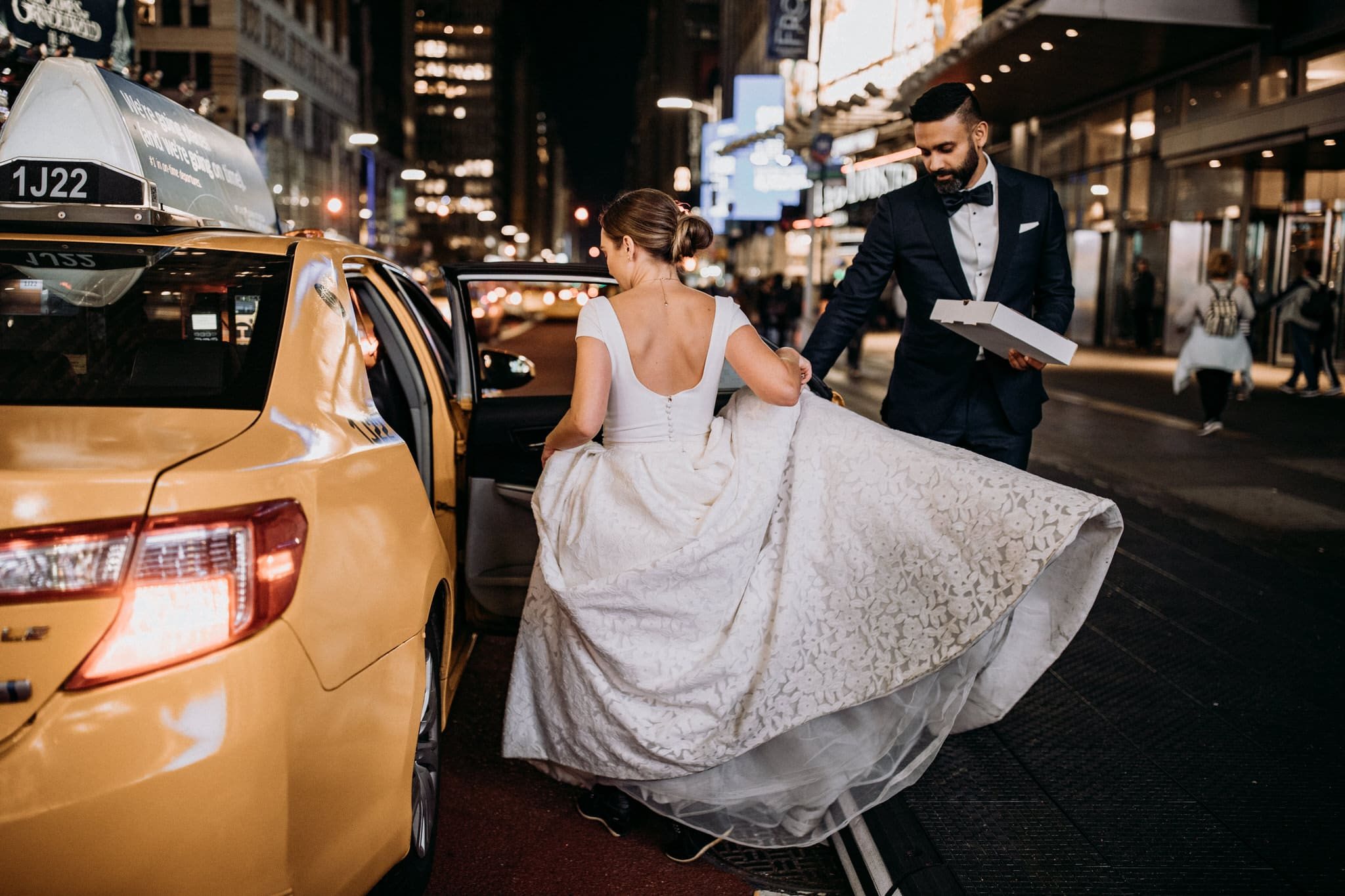 The bride and groom catch a taxi at Times Square in New York City. Wedding Photographer Brent Calis.