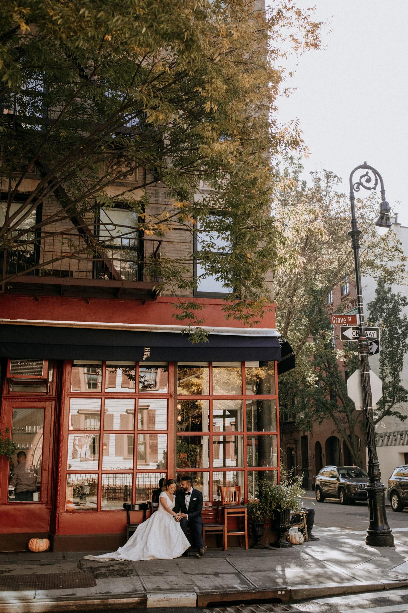 The bride and groom sit in front of a red bistro on their walk through the streets of New York. Wedding Photographer Brent Calis.