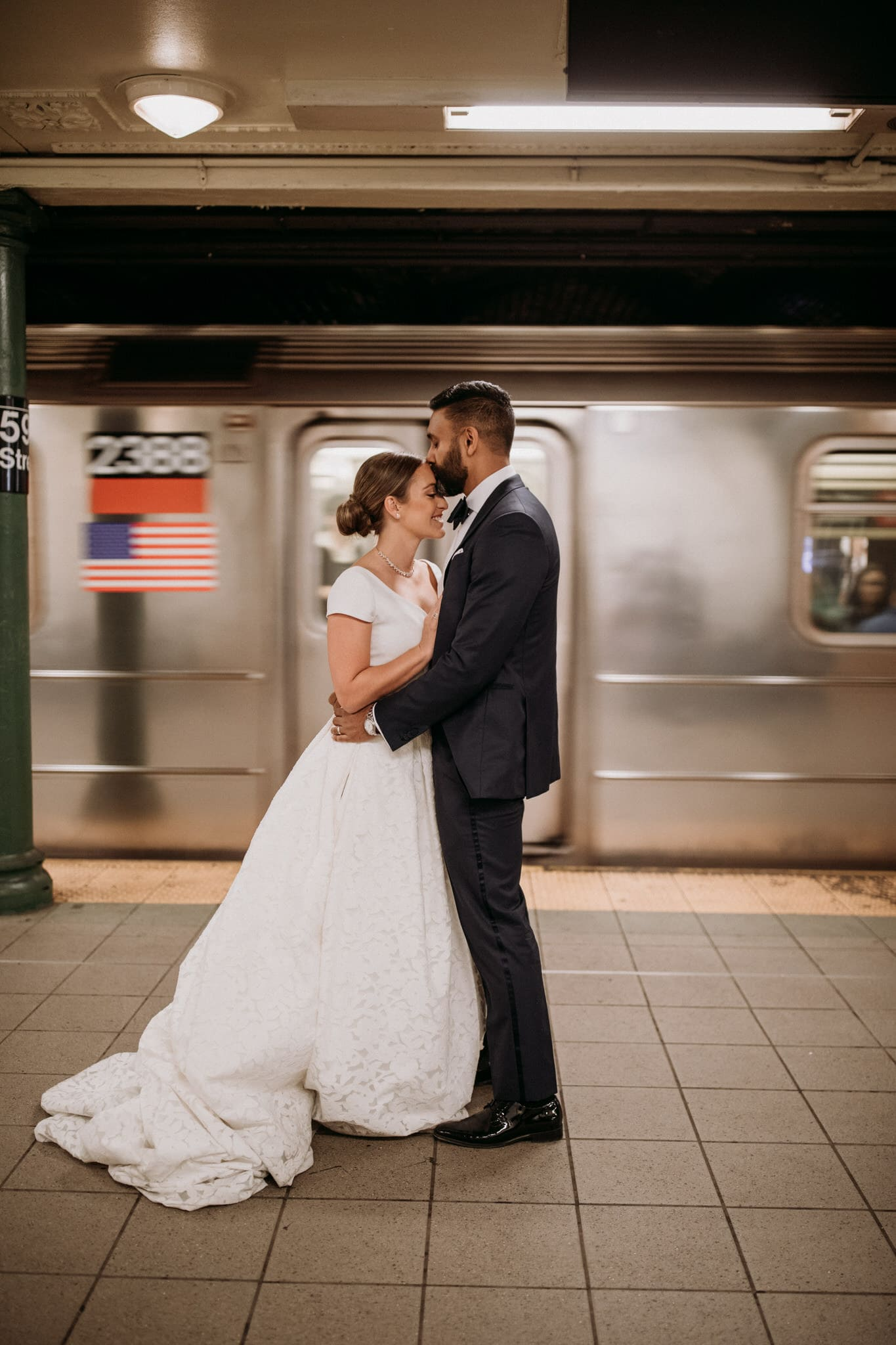 The bride and groom kiss on the subway platform in New York City. Wedding Photographer Brent Calis.